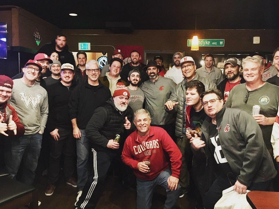 WSU head football coach Nick Rolovich in a gray Cougar windbreaker surrounded by patrons of Magnolia Village Pub.