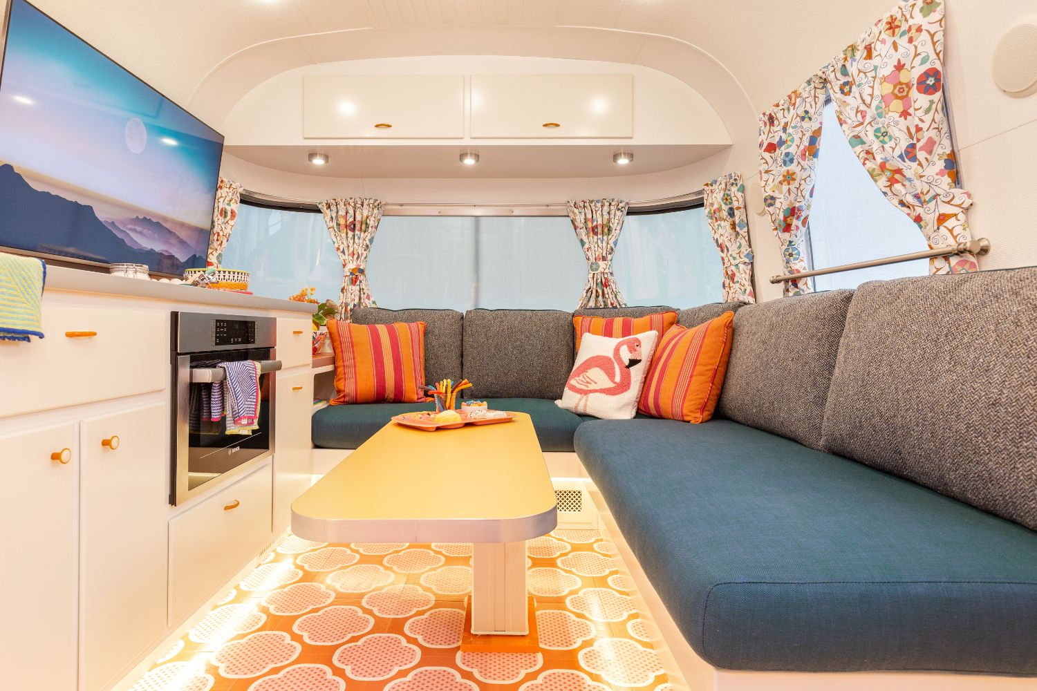 An interior view of a renovated Airstream travel trailer  has a teal blue bench seat, yellow table, and colorful print window coverings.