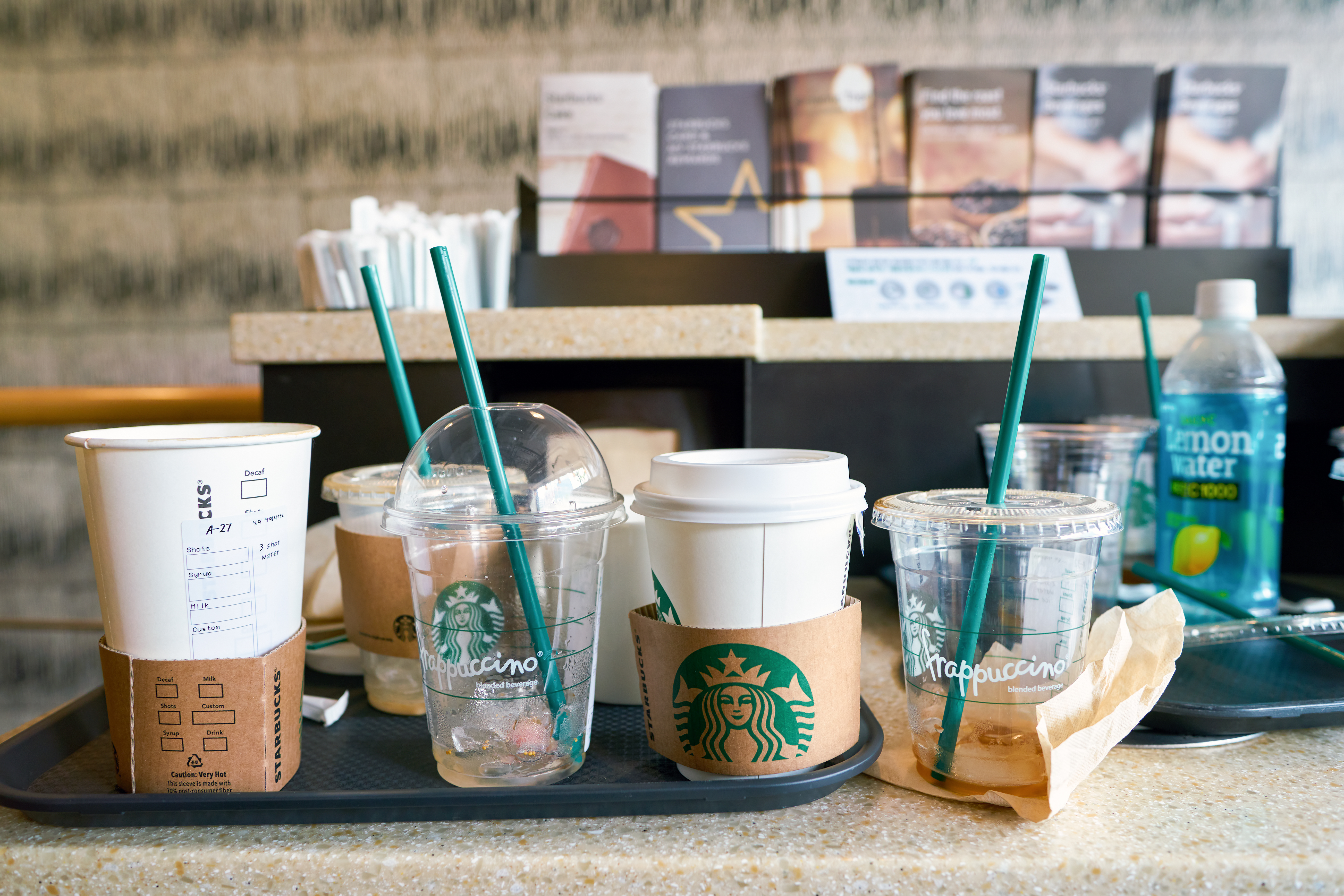 Discarded, empty plastic Starbucks cups on a tray.