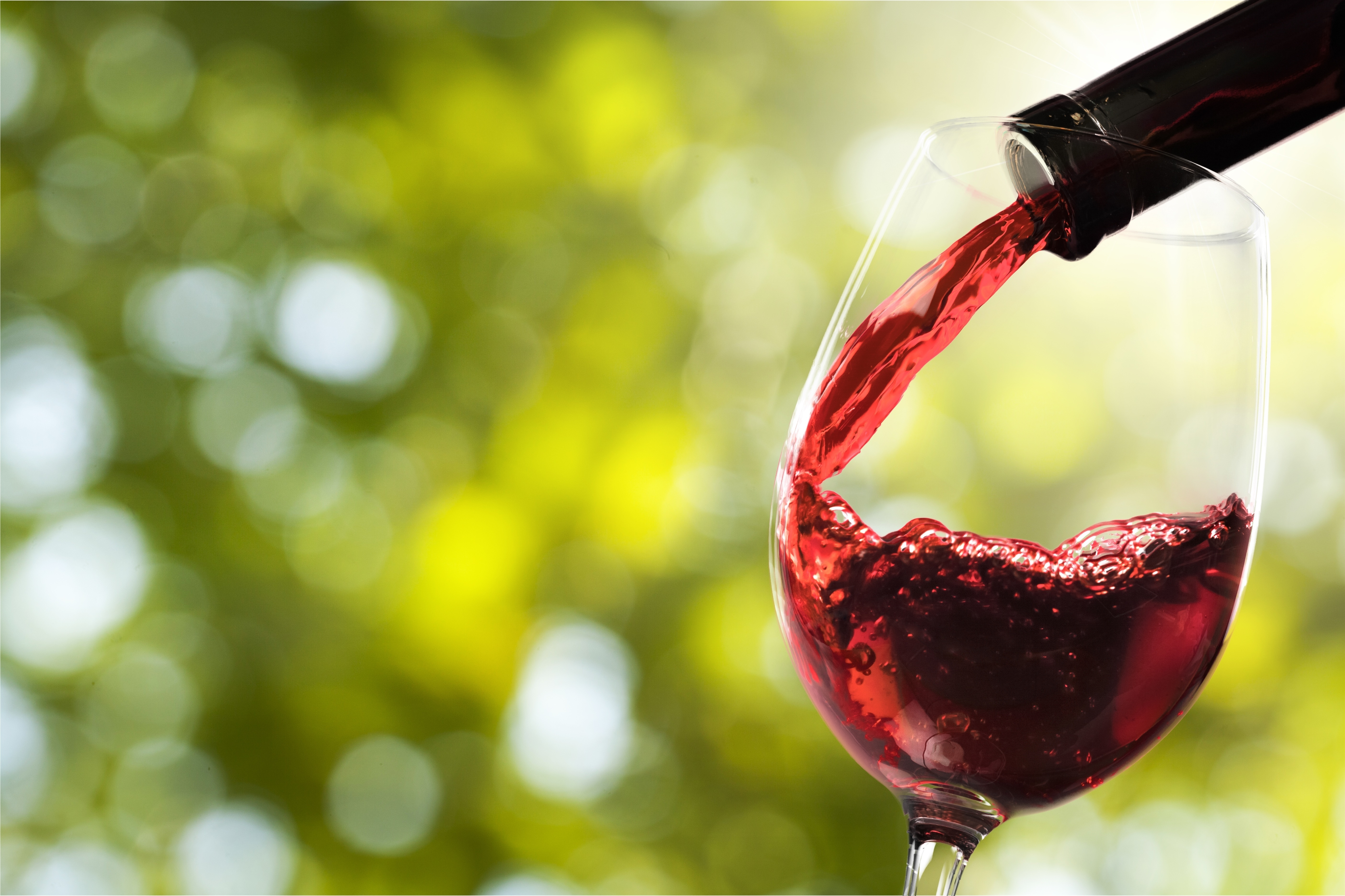 Red wine with a background of greenery