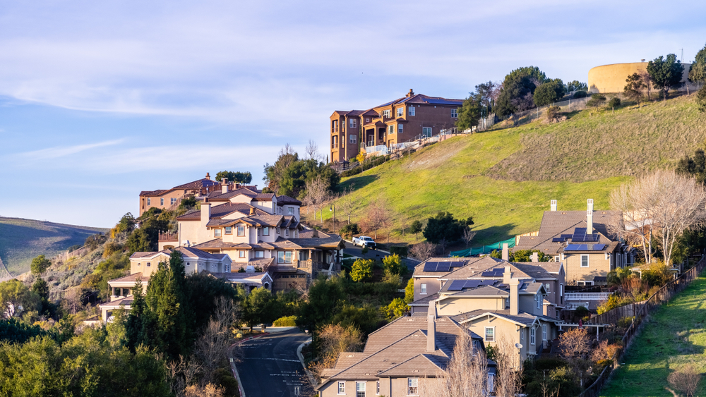 Residential neighborhood with multilevel single family homes, built on a hilly area; water tank visible on top of the hill.