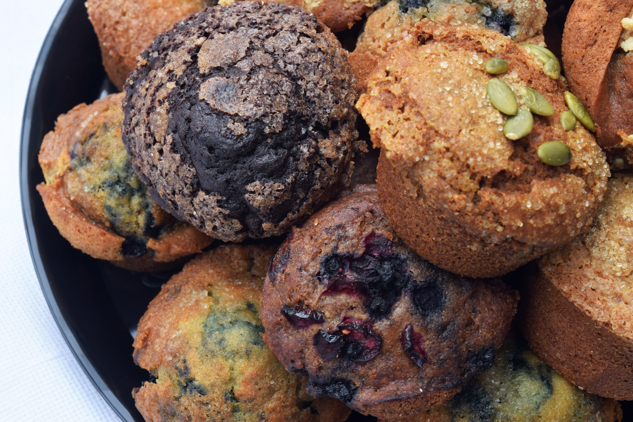 A plate of muffins sits on a white table