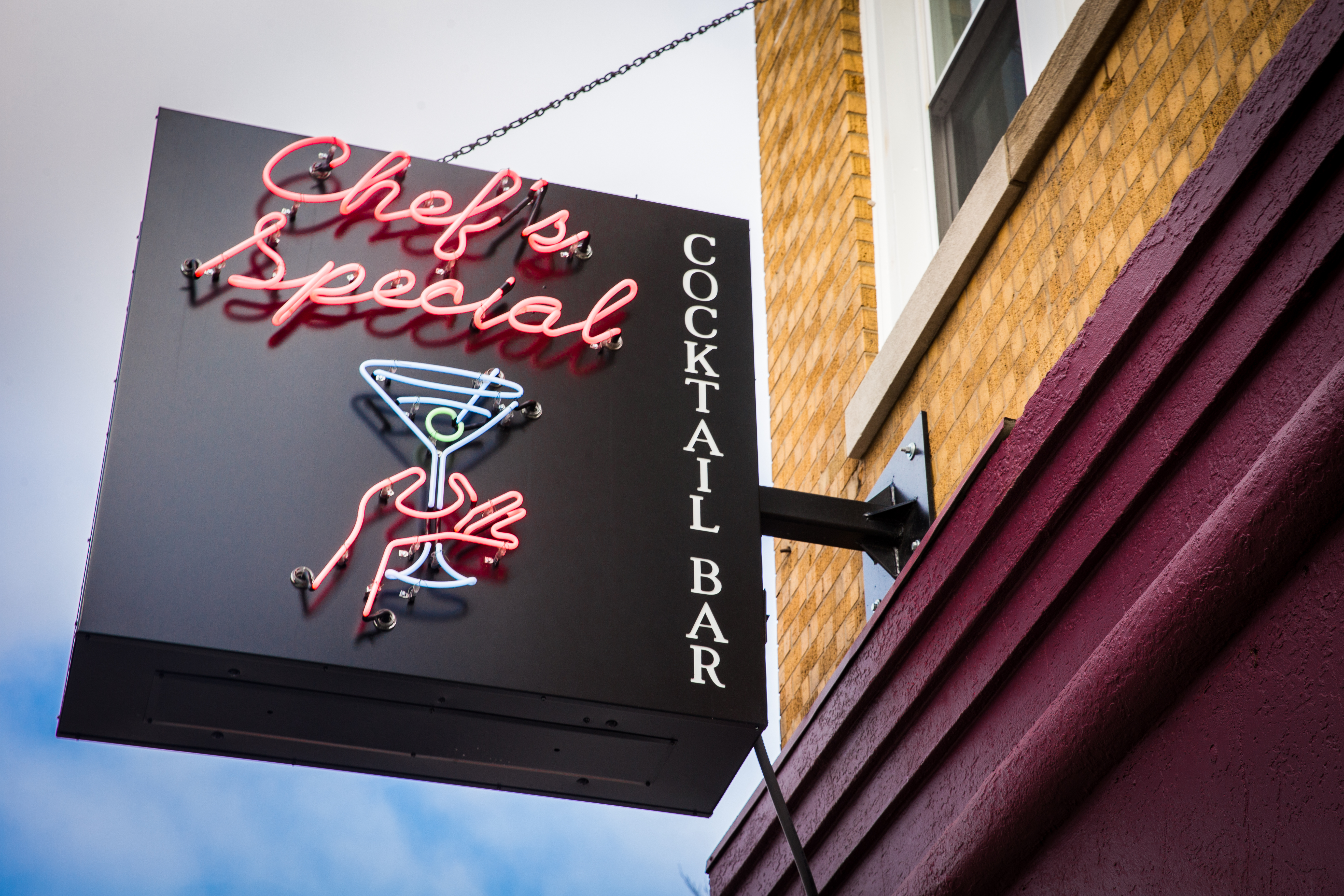 A black neon sign hanging outside a restaurant with a martini glass.