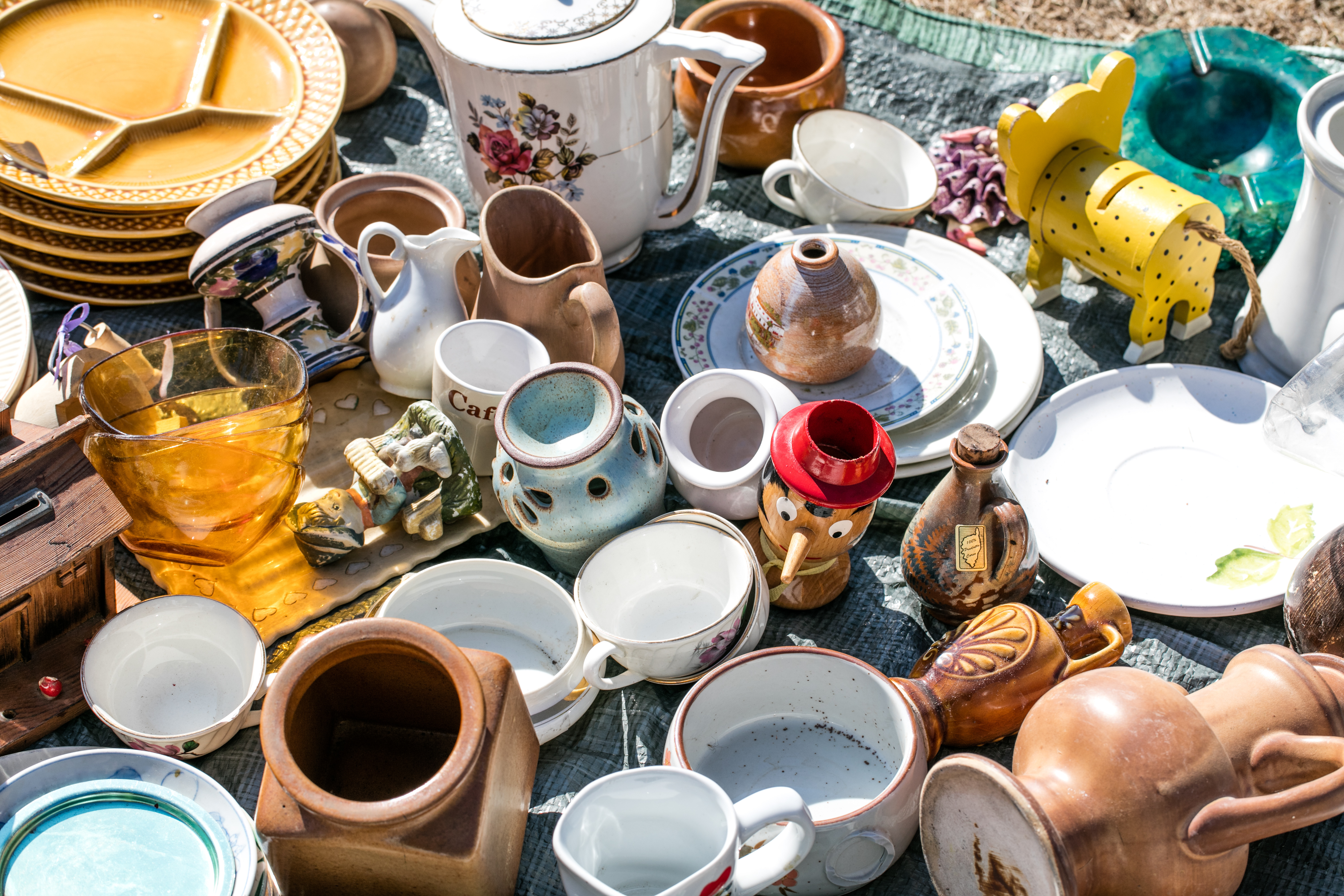 A table full of items like dishware, vases, and cups.