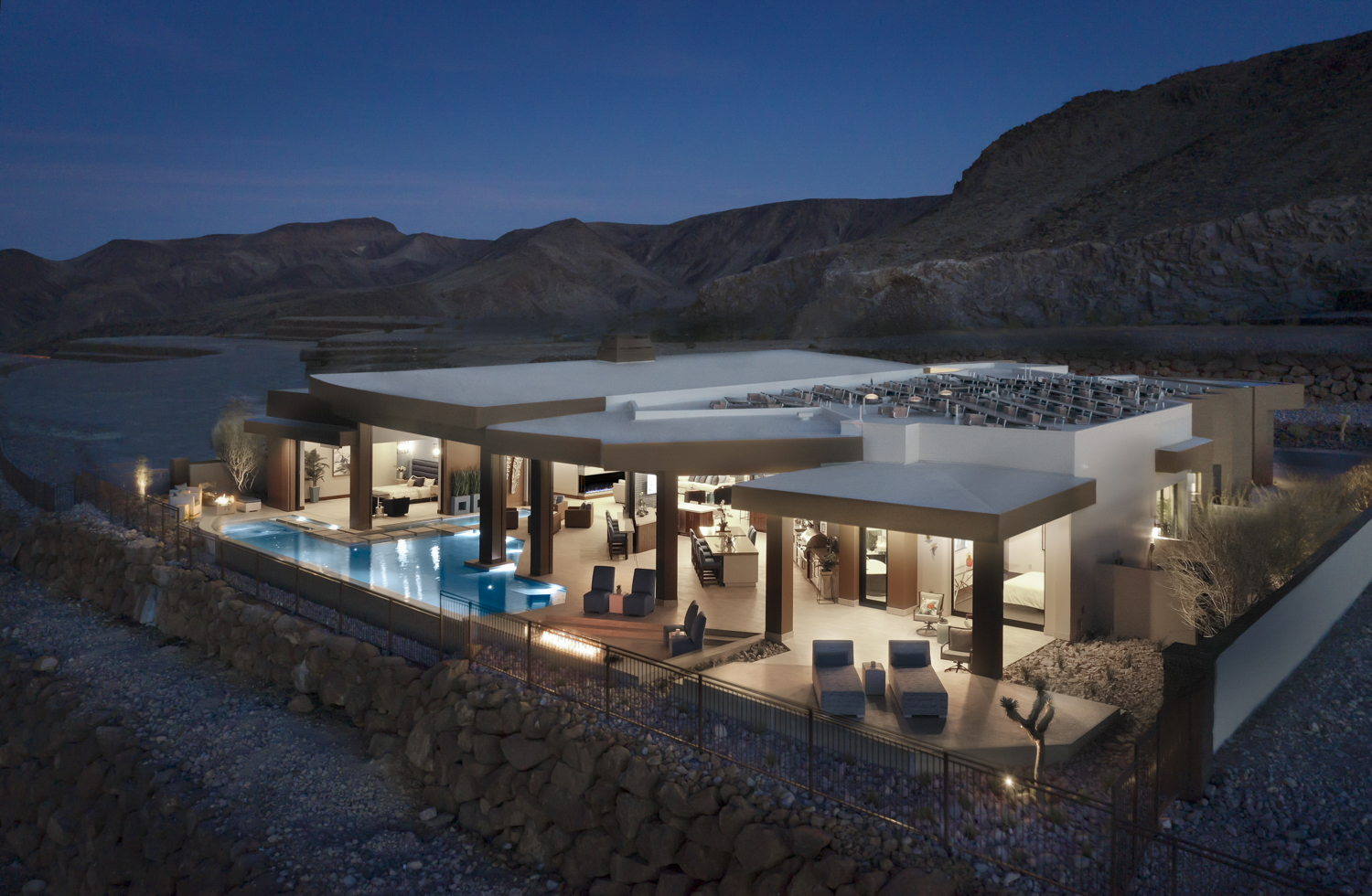 A sprawling contemporary home with a pool and wraparound deck is shown at night at the foot of a large mountain range in the desert.