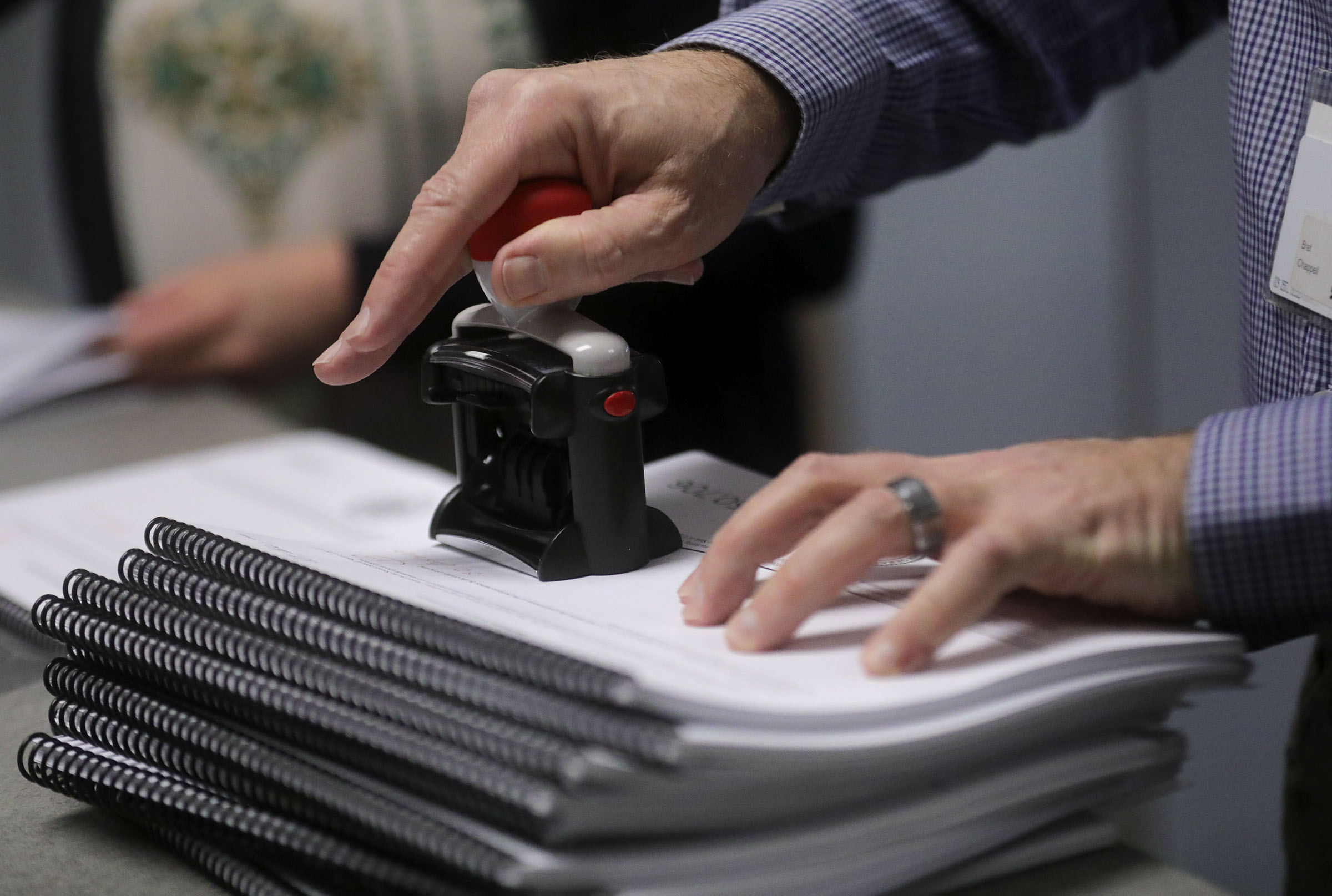 Bret Chappell stamps the received date on packets of signatures for the Utah tax reformreferendum at the Salt Lake County Clerk's Office in Salt Lake City on Tuesday, Jan. 21, 2020.