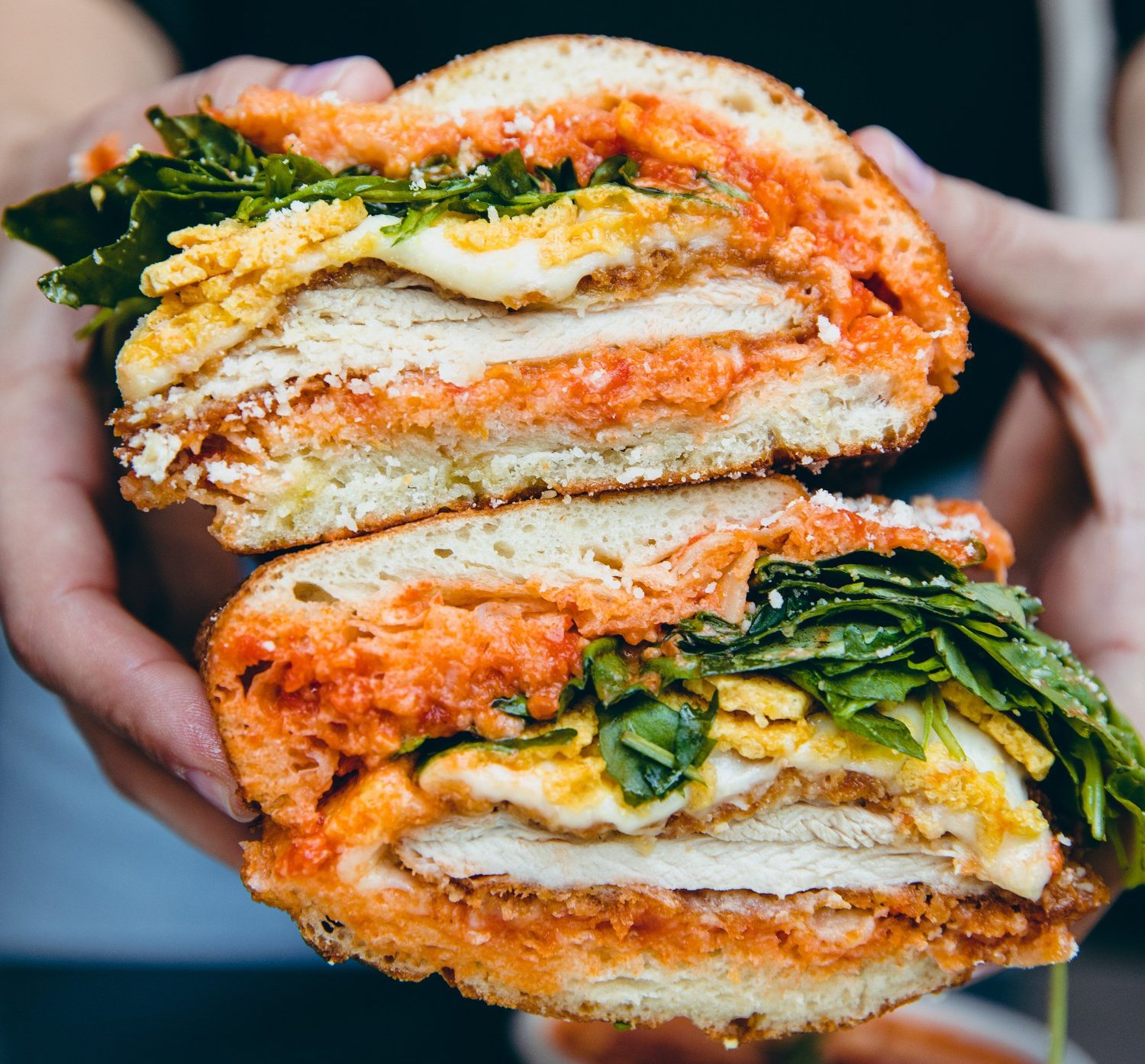 A chicken parm sandwich held open in two hands.