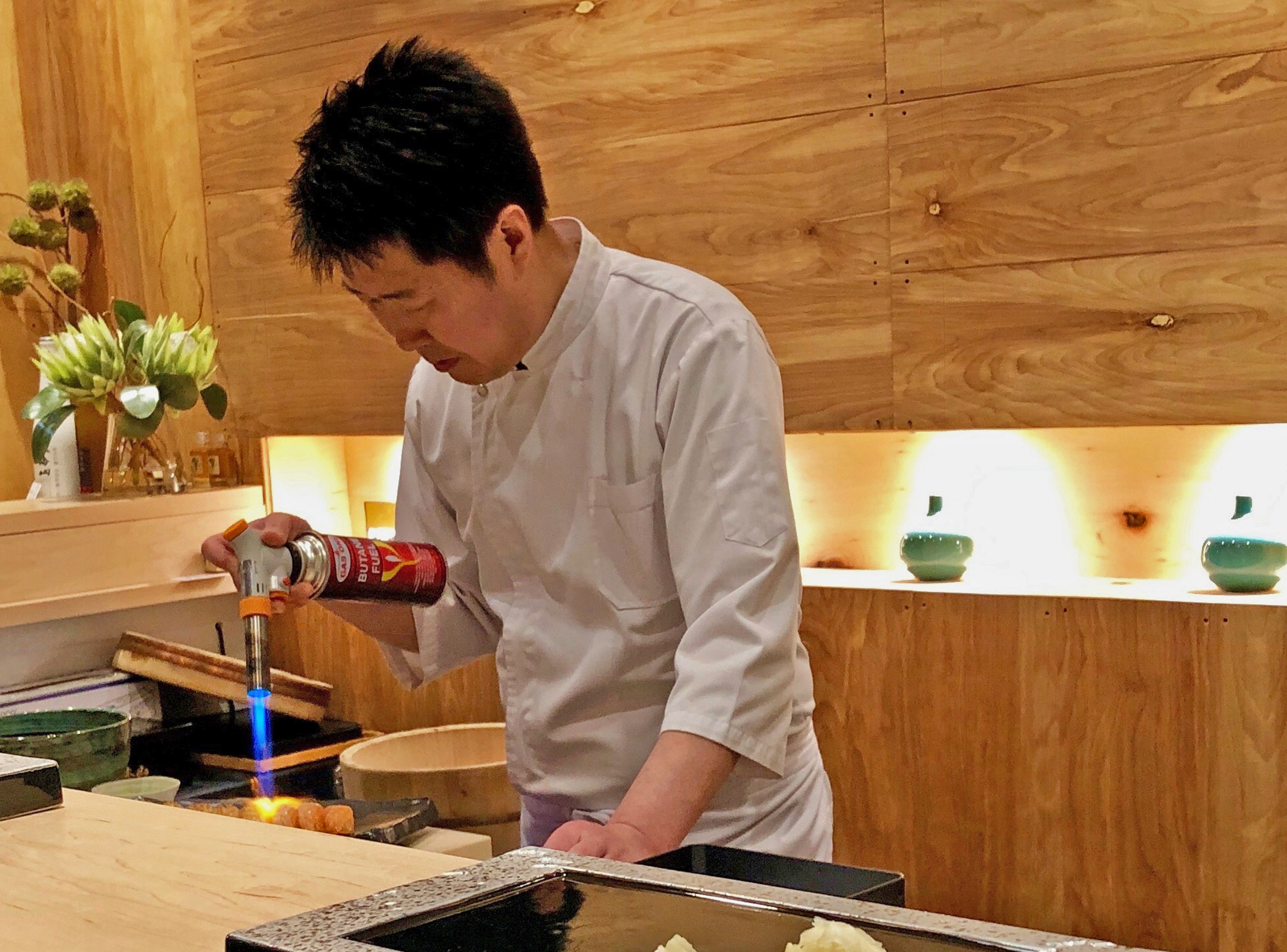 Chef Sangtae Park applies a blowtorch to raw fish.