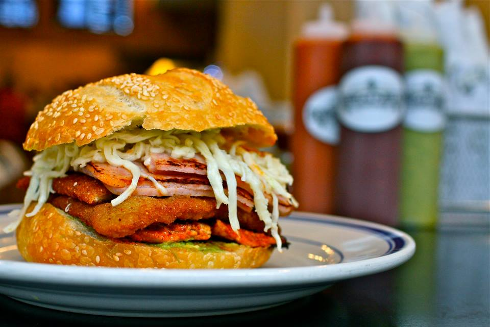A large Mexican ham sandwich on a sesame seed bun with lots of toppings.