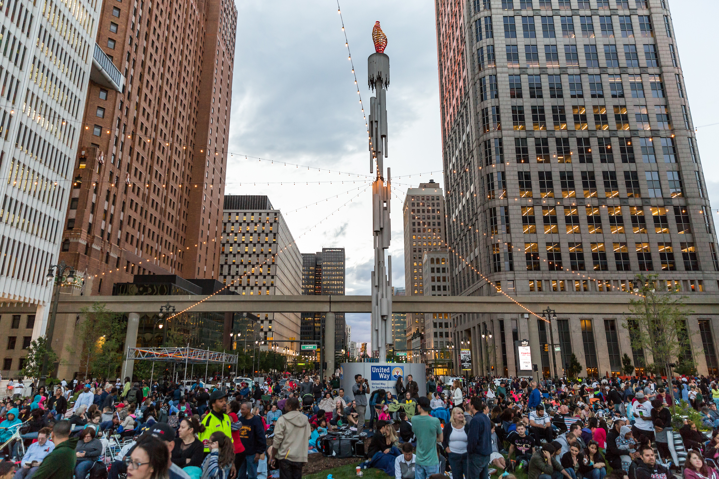 A big gathering at a downtown park. People stand or sit in foldable chairs around a metal statue. Tall buildings surround the mass of people.