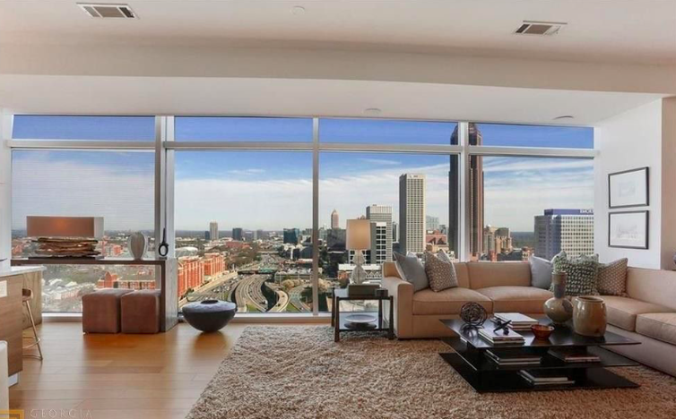 A large condo with huge windows looking out onto the city of Atlanta.