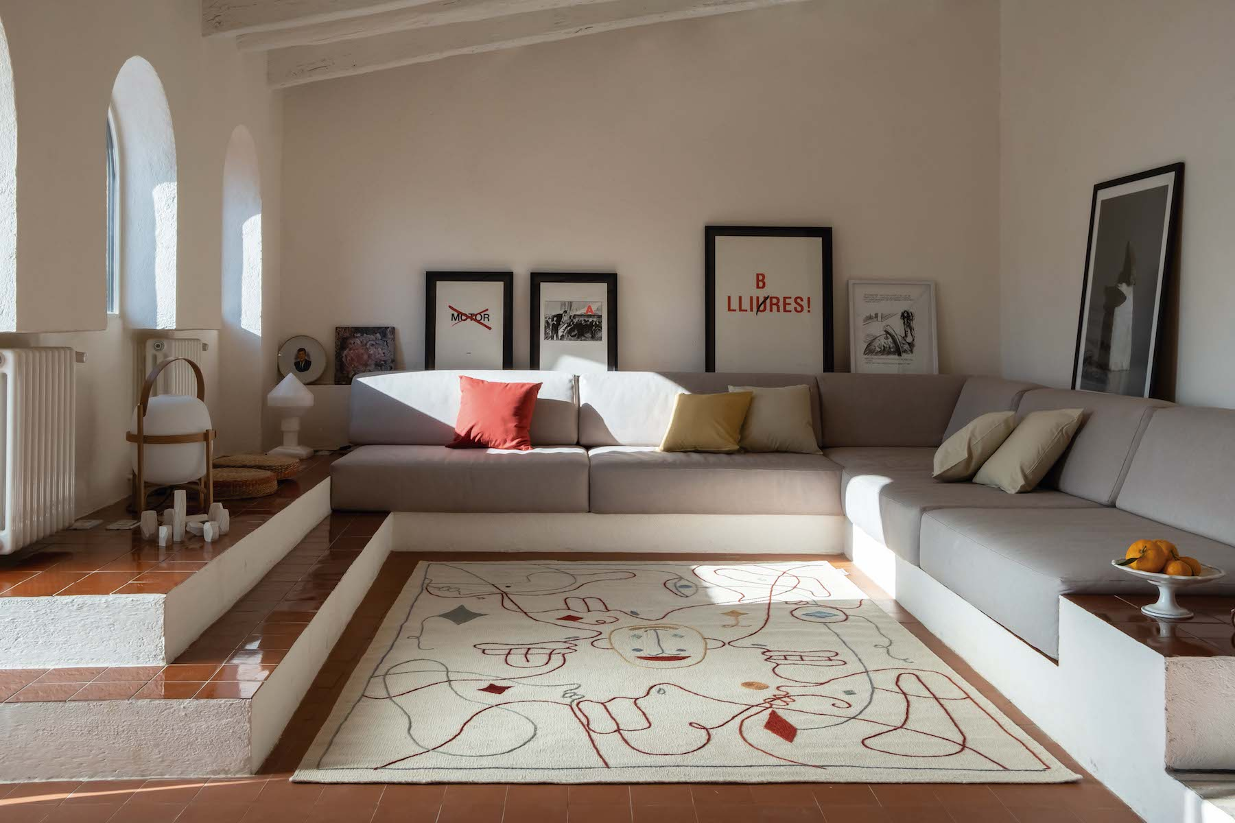 Cream colored rug with colorful lines sits in the center of a living room with gray sofa.
