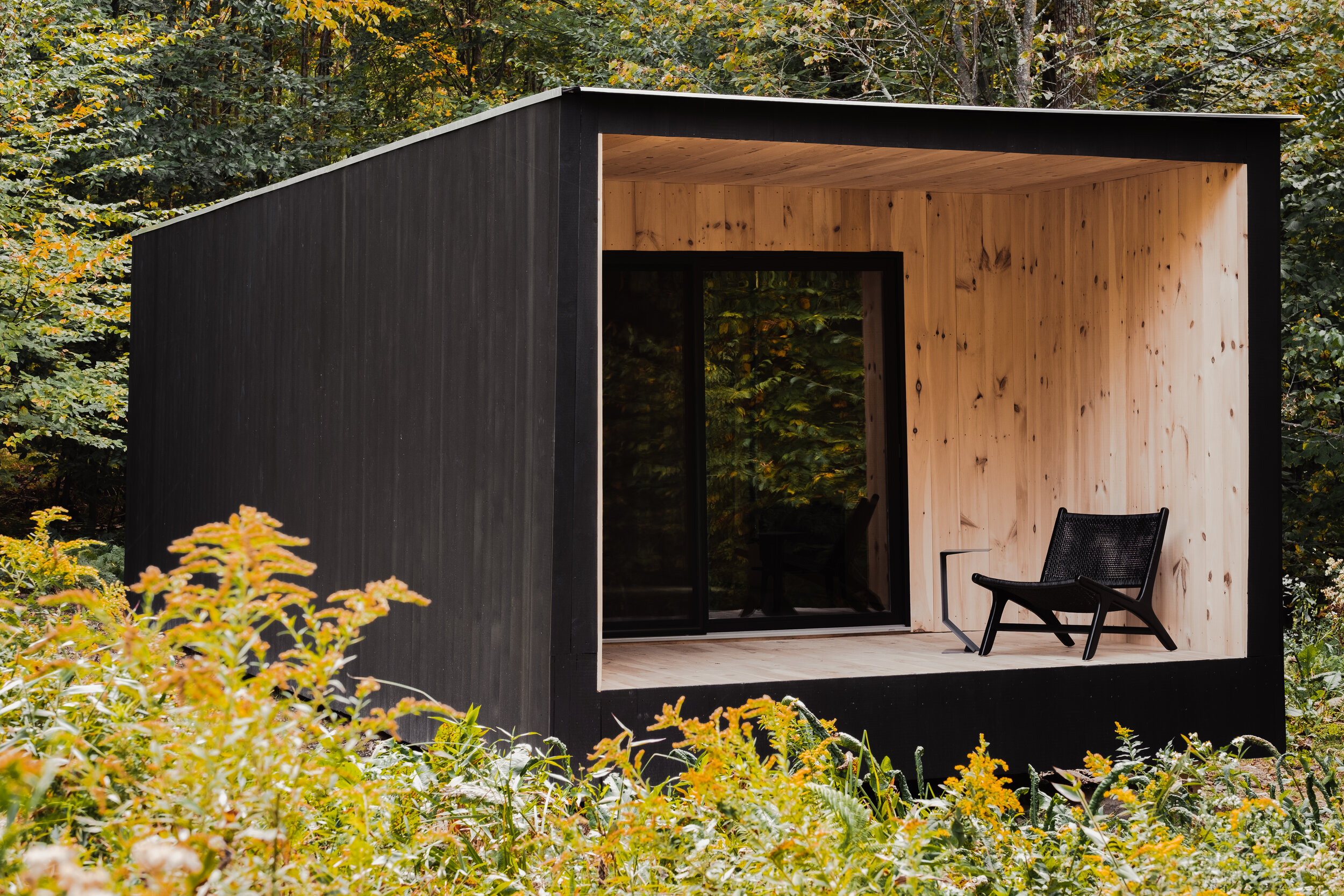 Cabin with charred timber facade and covered porch.