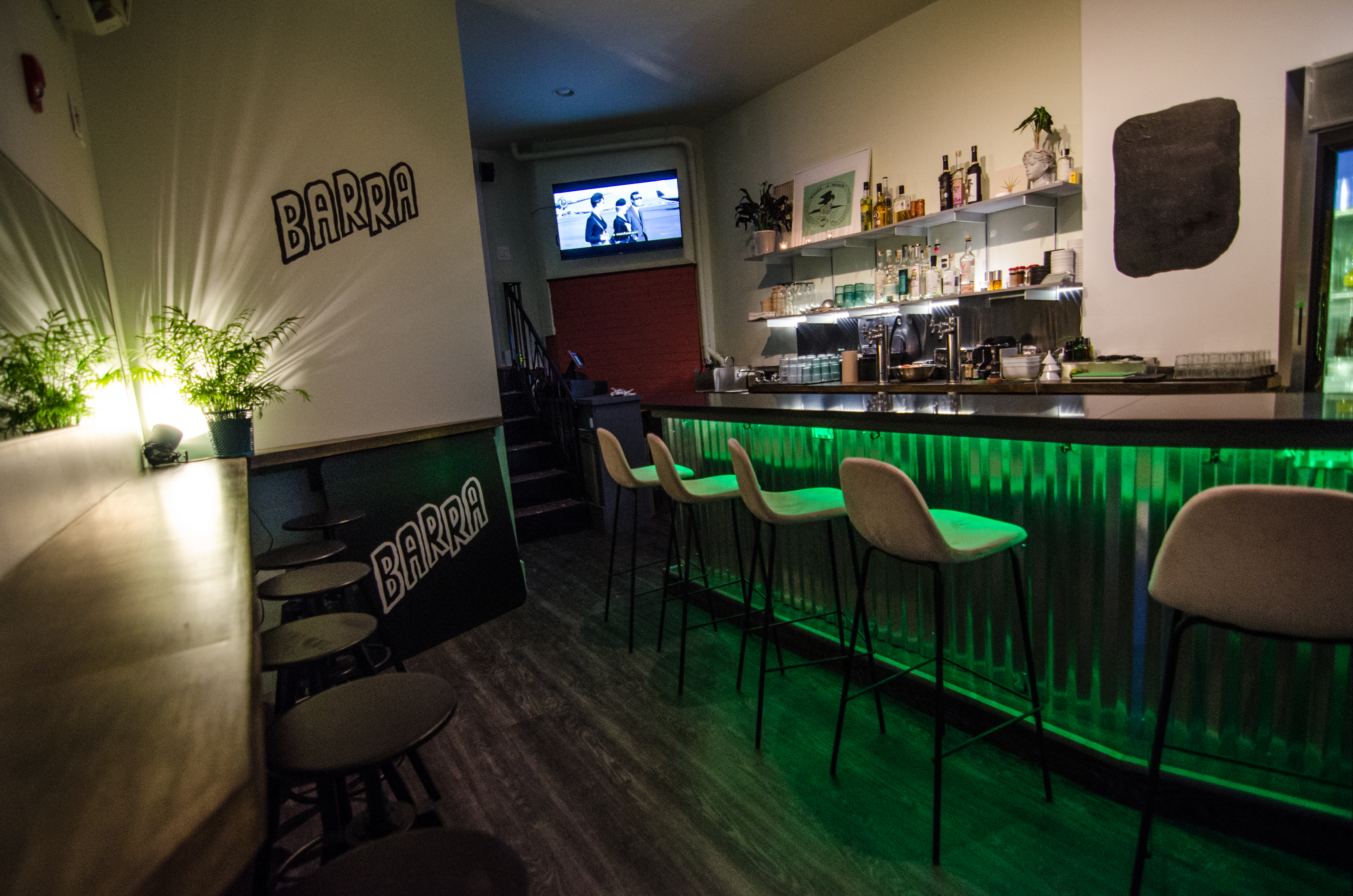 Interior of a small bar, dimly lit with green accents. The bar itself is lined with corrugated galvanized aluminum. The bar's name, Barra, is hand-painted in thick black paint on the wall, and a spotlight casts lines through the leaves of a potted plant.