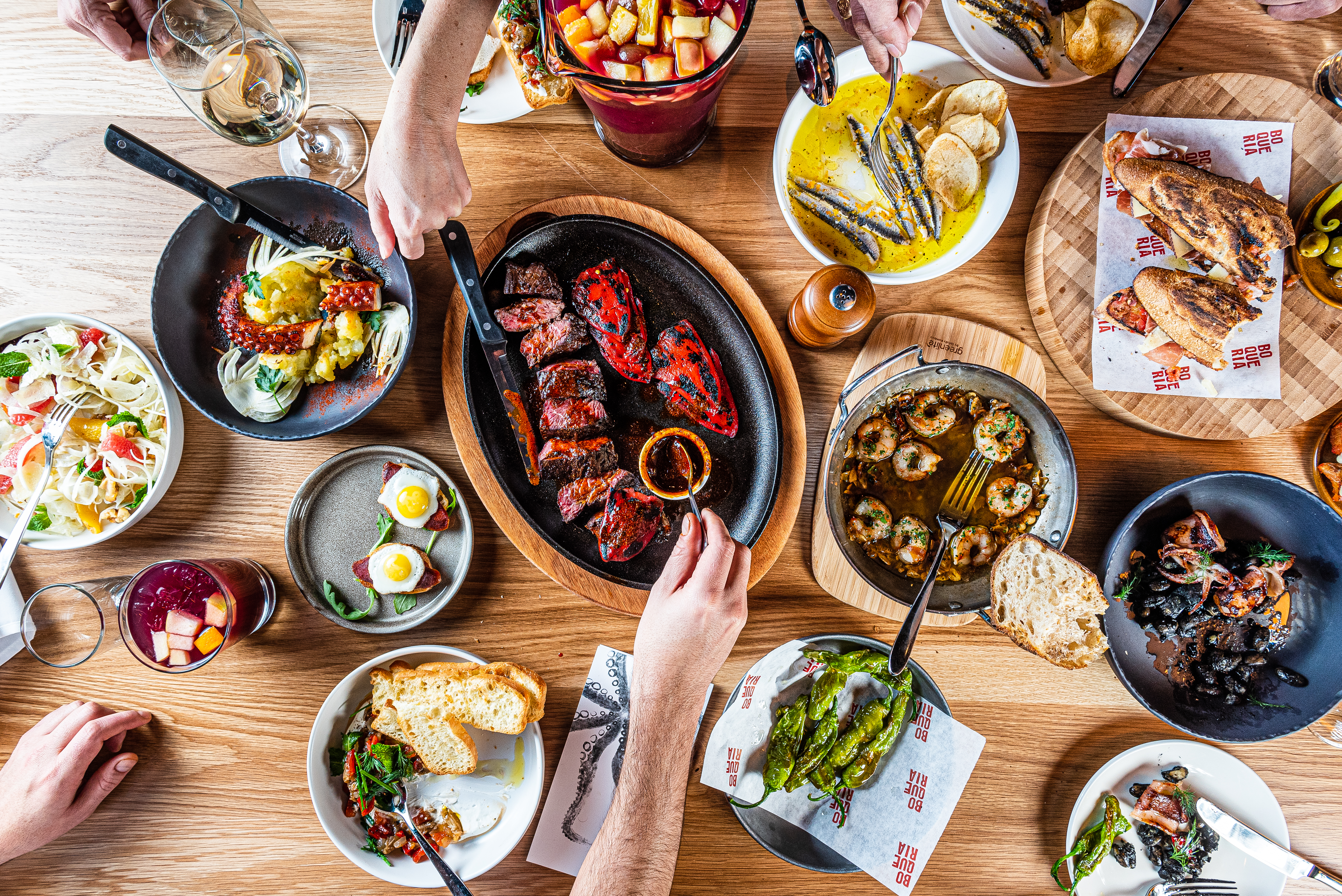 A wooden table filled with plates of small Spanish tapas.