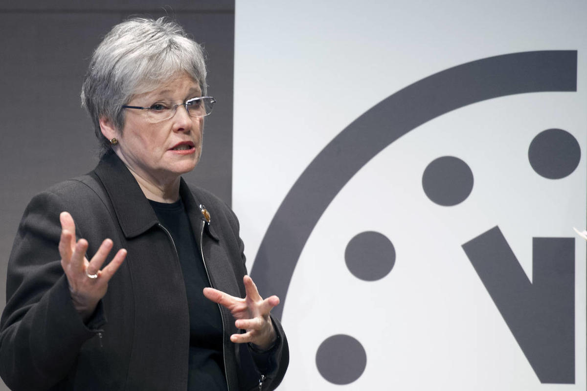 Kennette Benedict, executive director, Bulletin of the Atomic Scientists, stands beside the old Doomsday Clock which showed five minutes until midnight during a news conference to announce the new clock reads three minutes until midnight, Thursday, Jan. 2