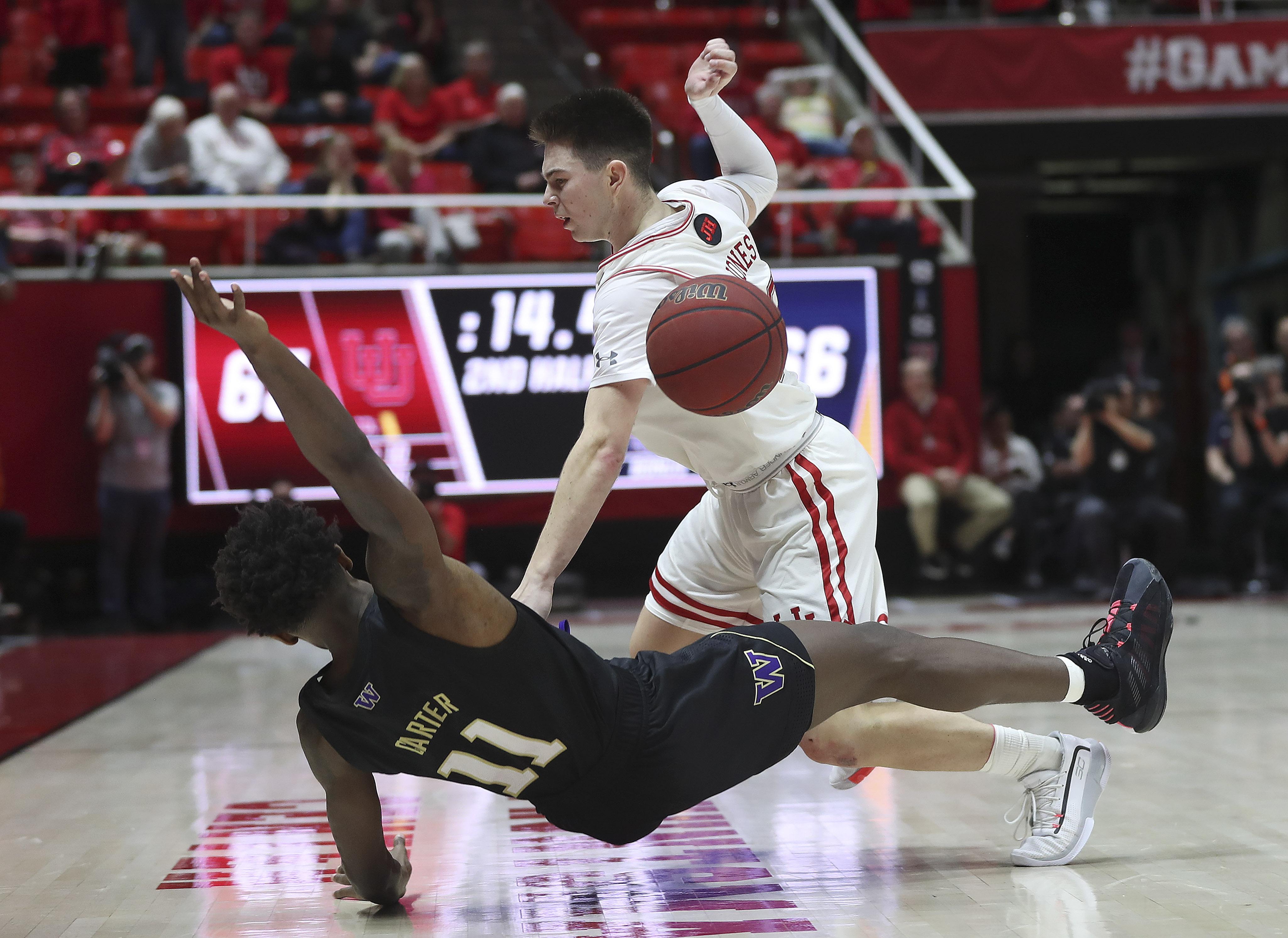 Utah Utes guard Rylan Jones (15) and Washington Huskies guard Nahziah Carter (11) get tangled up in Salt Lake City on Thursday, Jan. 23, 2020. The Utes won 67-66.
