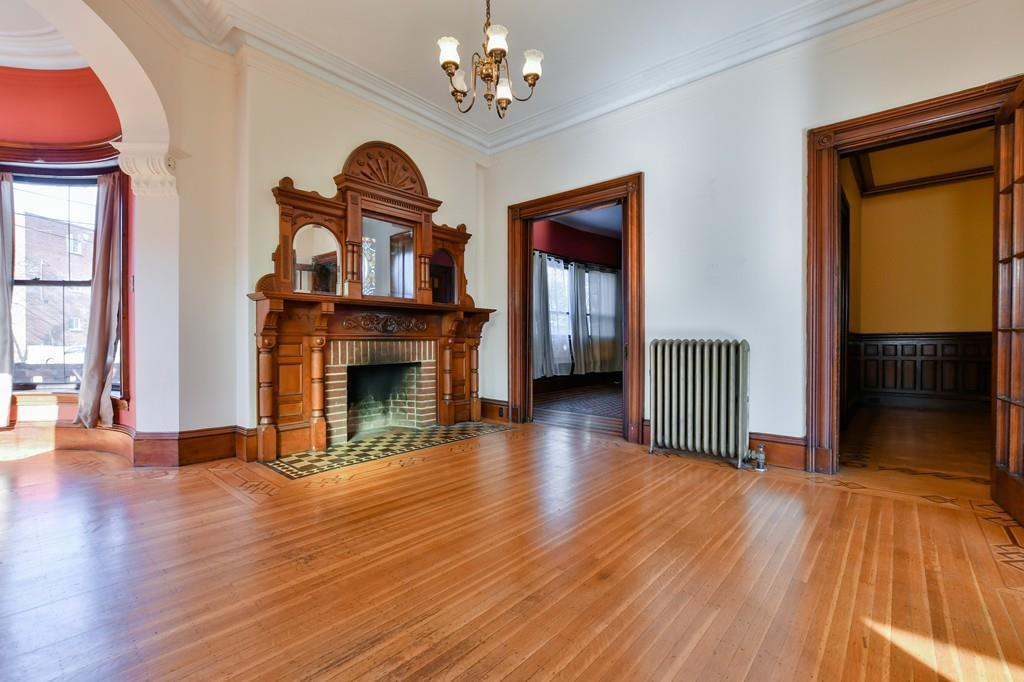 A large living room with two doors off it, and there's an ornate fireplace dominating the room; it's empty otherwise.