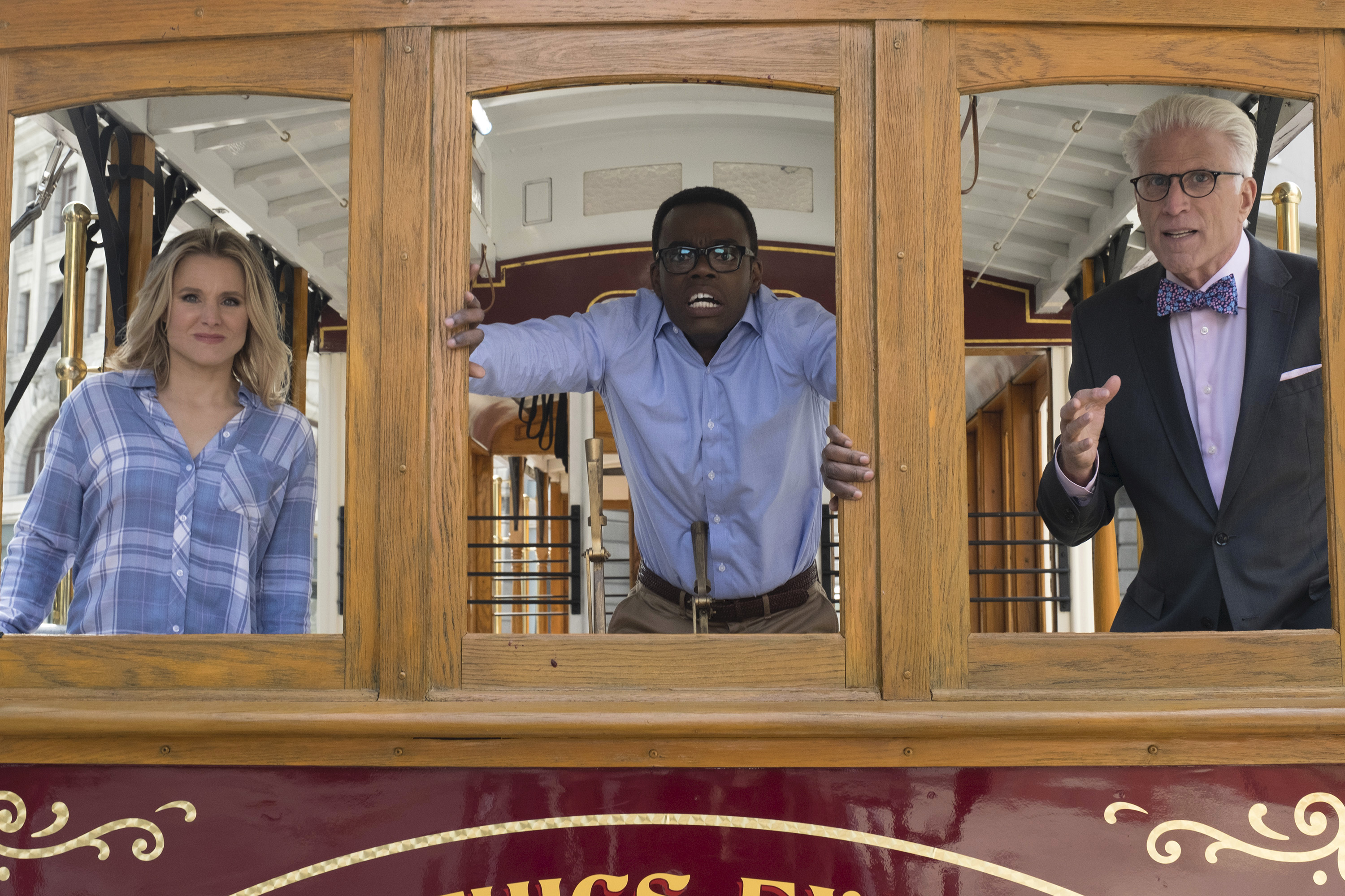 "Three characters from the TV show ""The Good Place"" stand in the front windows of a trolley."