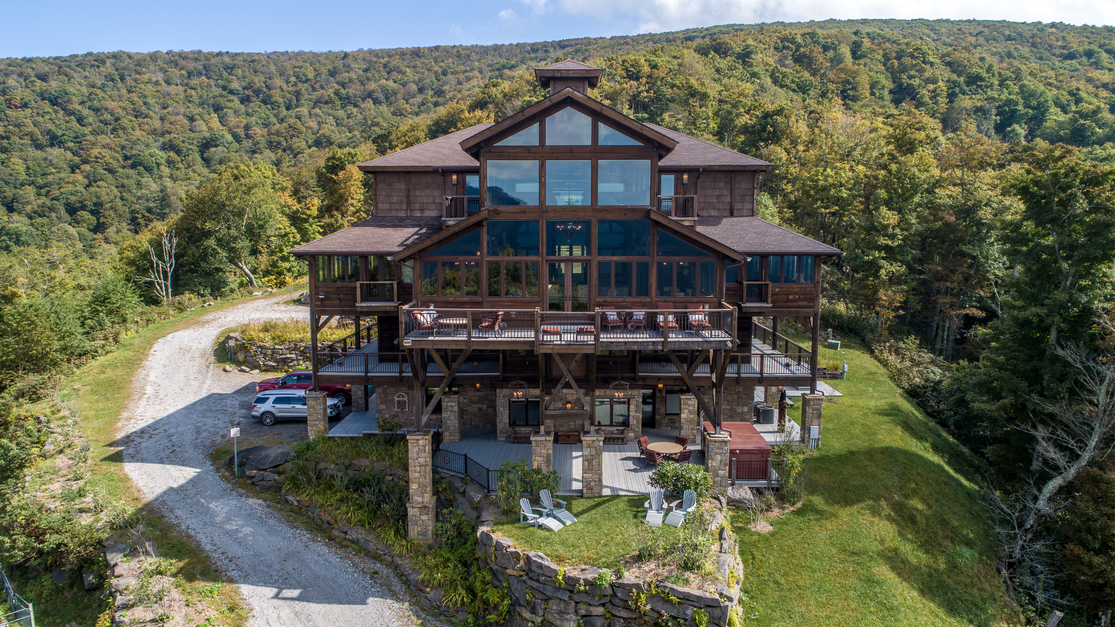 An aerial exterior view of a large timber home surrounded by mountains.