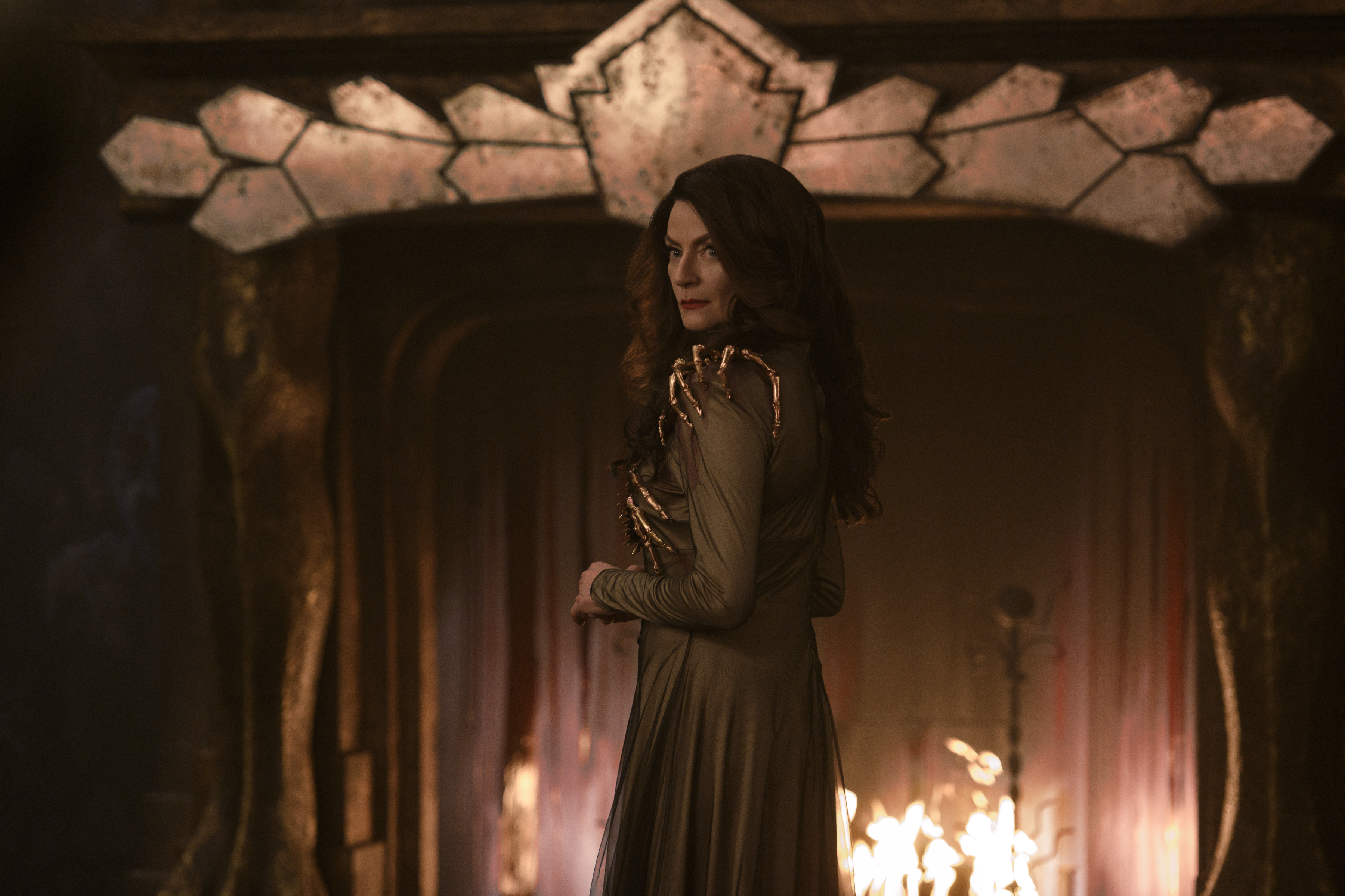 A red-headed woman in a green gown accented with golden finger-bones looks over her shoulder while standing in front of a dramatic fireplace.