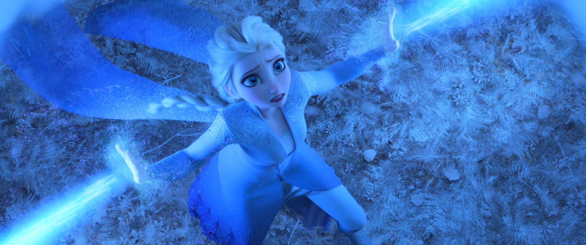 Seen from above, Queen Elsa looks frightened while using her ice powers to hold back an unseen enemy in Frozen II.