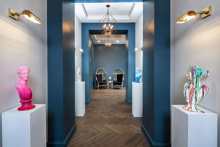 A long white and blue hallway at an apartment with wood floors and statues.