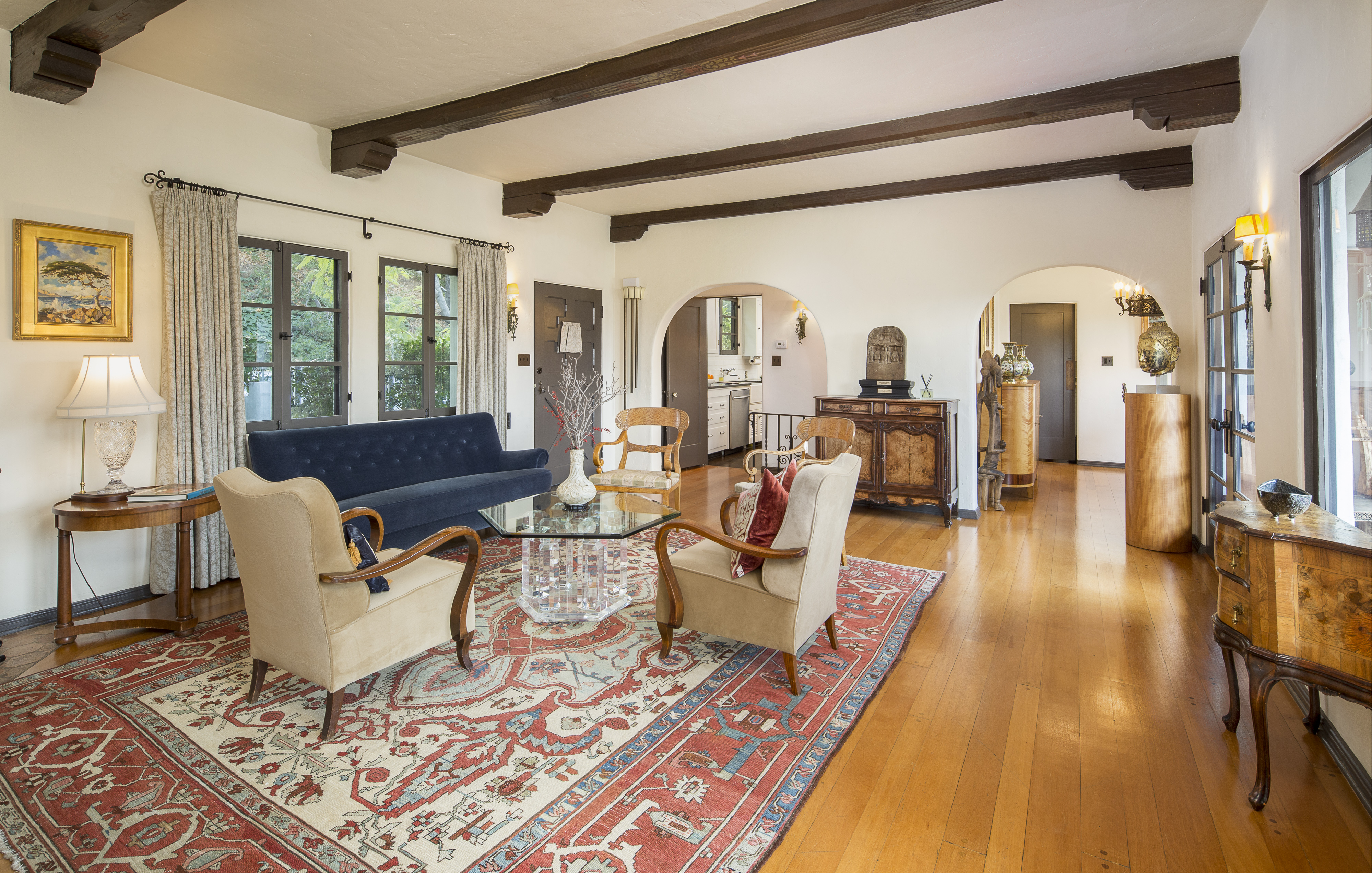 A room with many windows, lots of indirect sunlight, hardwood floors, and arched doorways.
