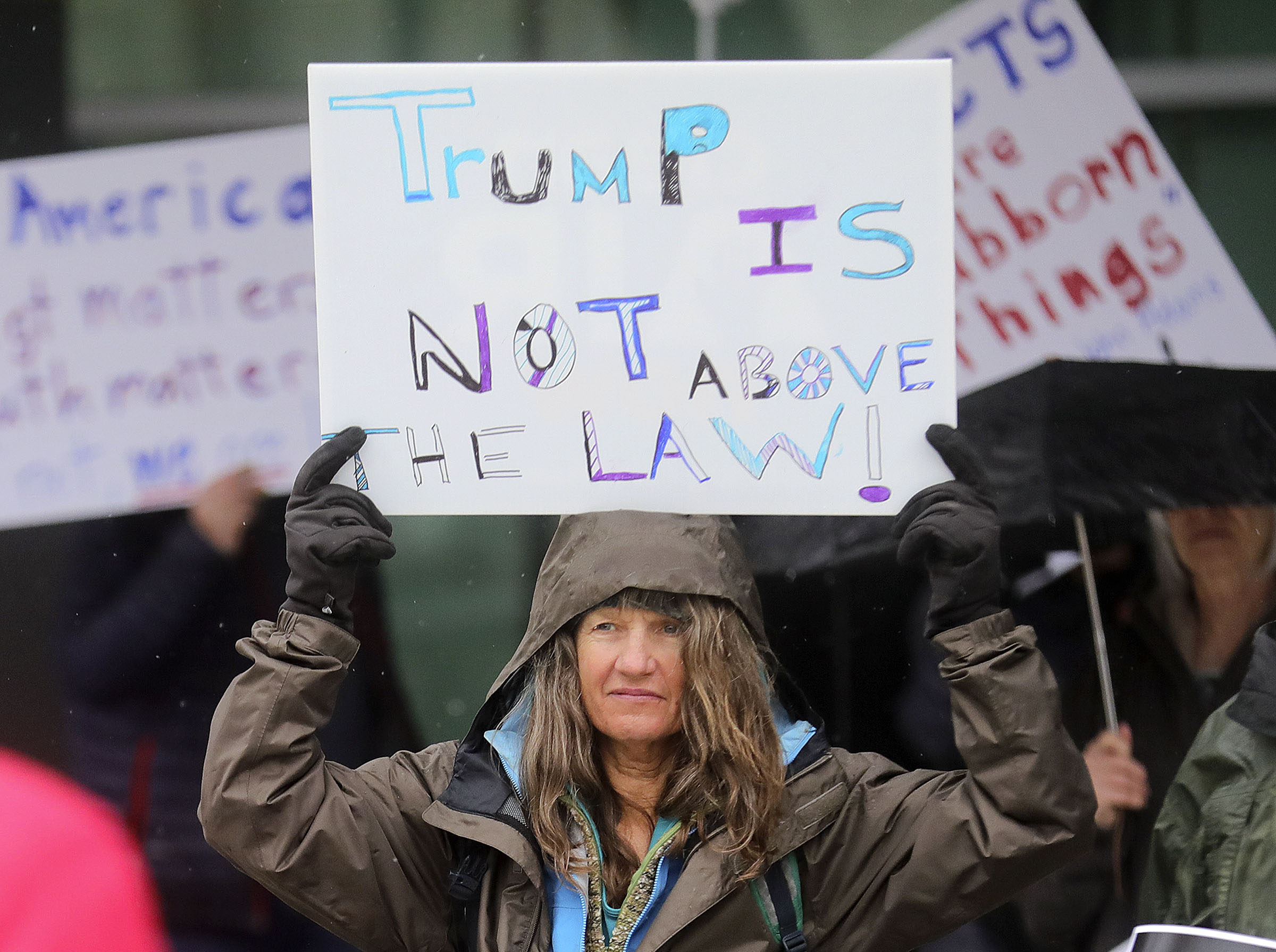 Activists rally for a fair impeachment trial outside of Sen. Mitt Romney's office in Salt Lake City on Friday, Jan. 24, 2020.