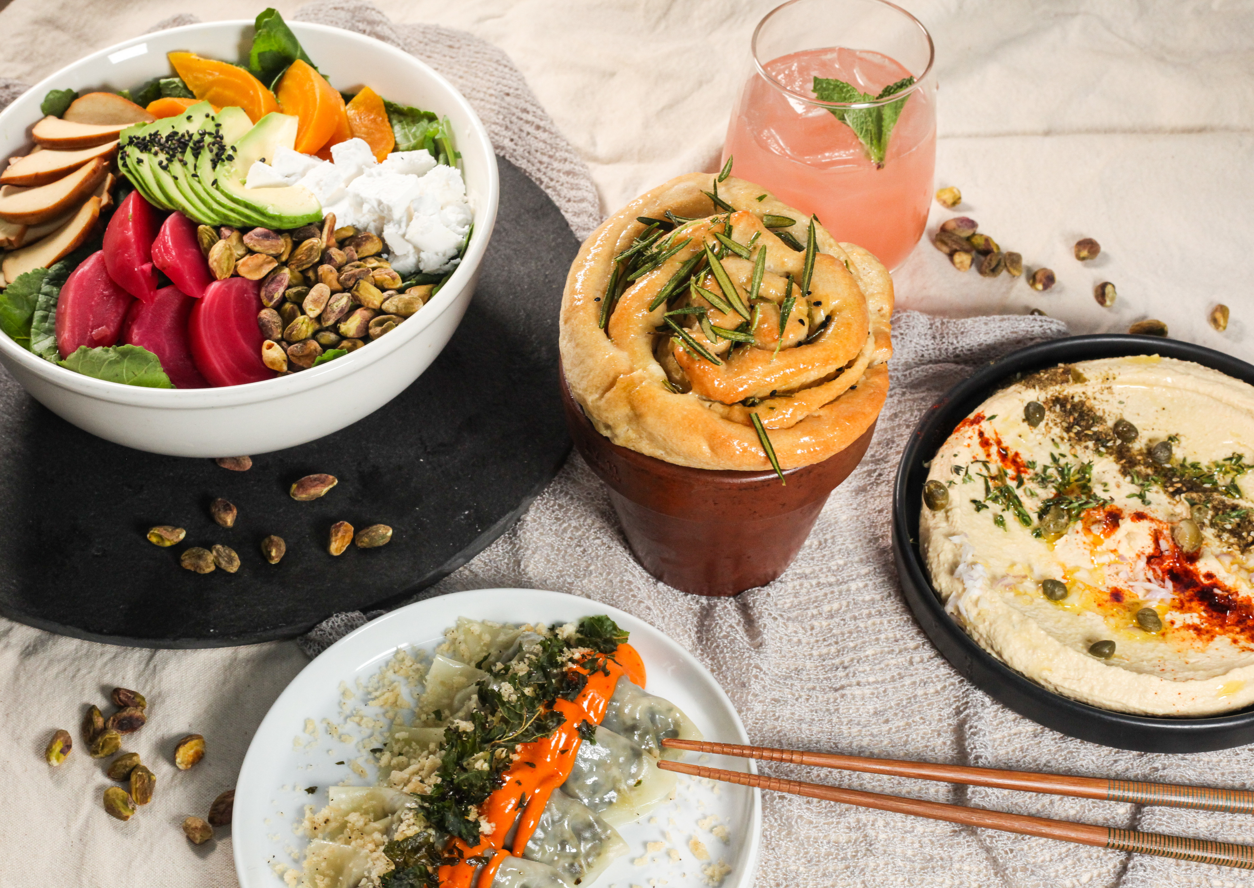 A spread of dishes from Beyond Sushi, including a salad packed with colorful veggies, a white plate topped with a line of dumplings, and a black plate of hummus.
