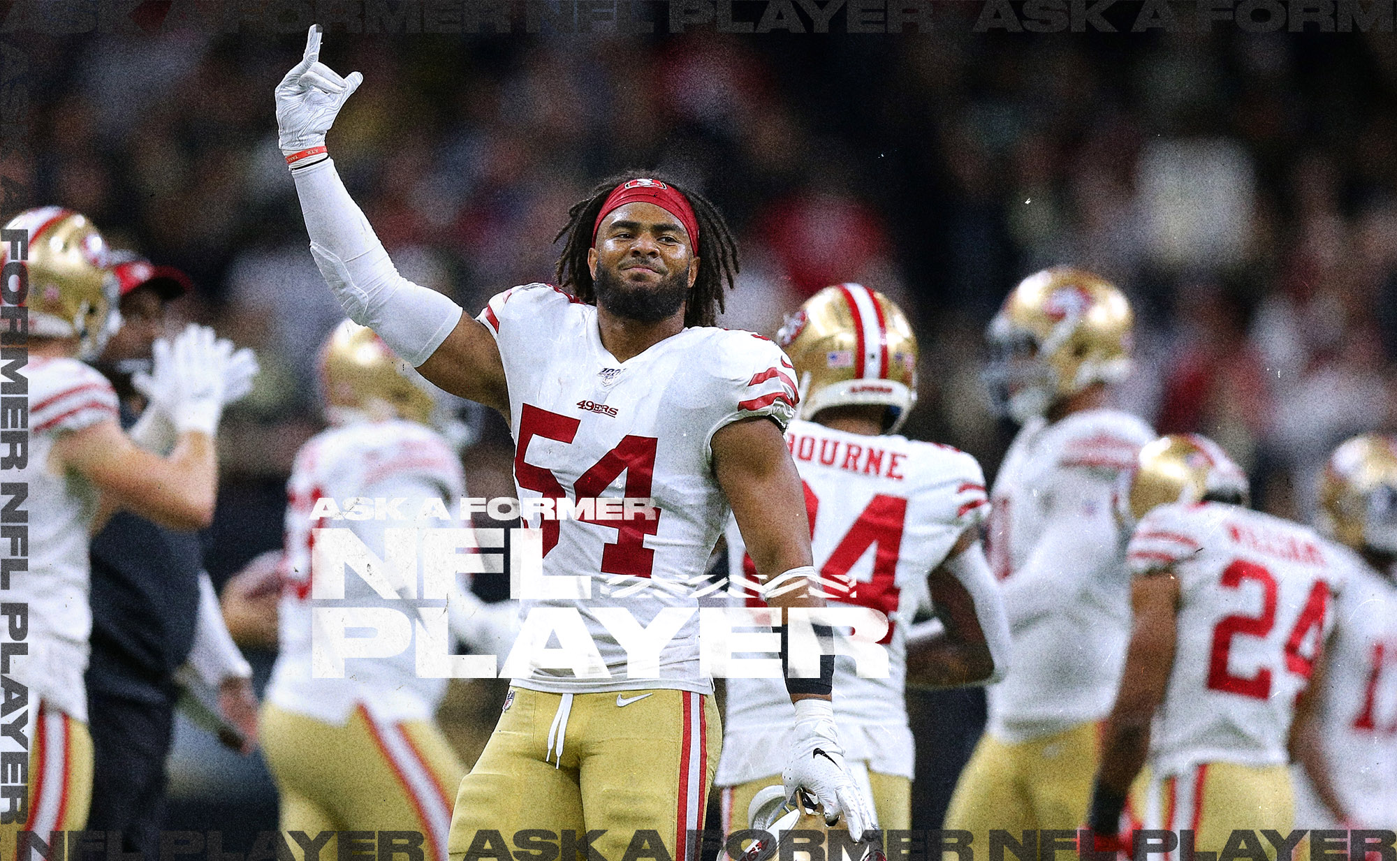 49ers LB Fred Warner holds his right arm up while looking at the crowd, with his teammates huddled behind him