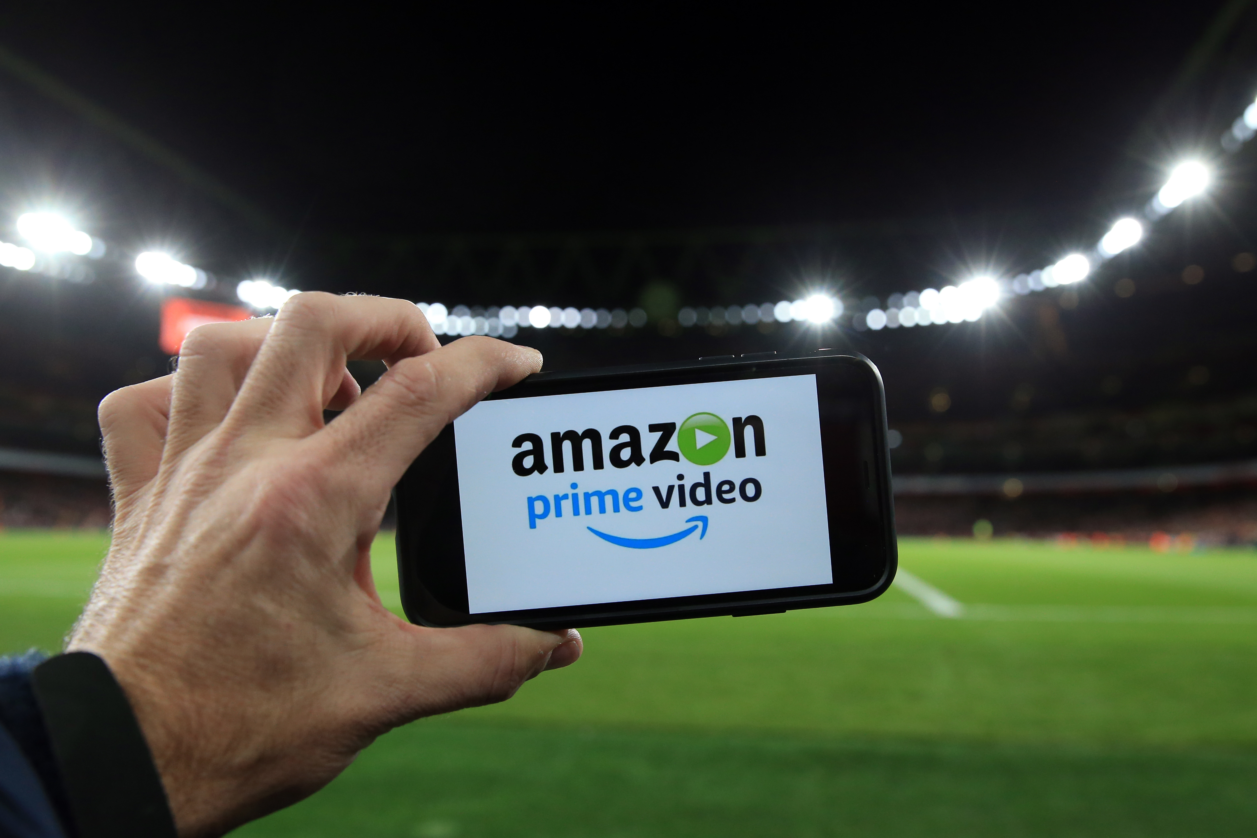 "A hand holding a phone with ""Amazon Prime Video"" on the screen."
