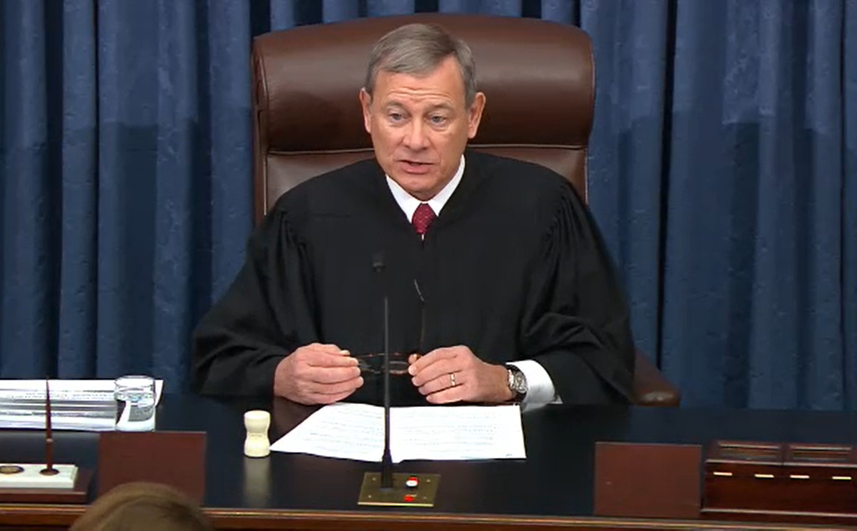 Supreme Court Chief Justice John Roberts sitting at a desk wearing his judicial robe.