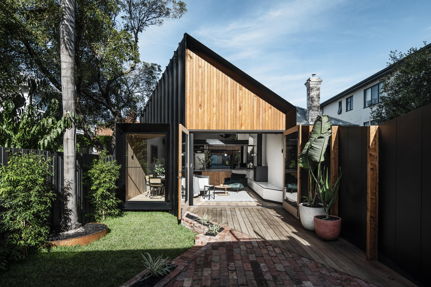 Timber and metal house with angled roof and wooden porch.