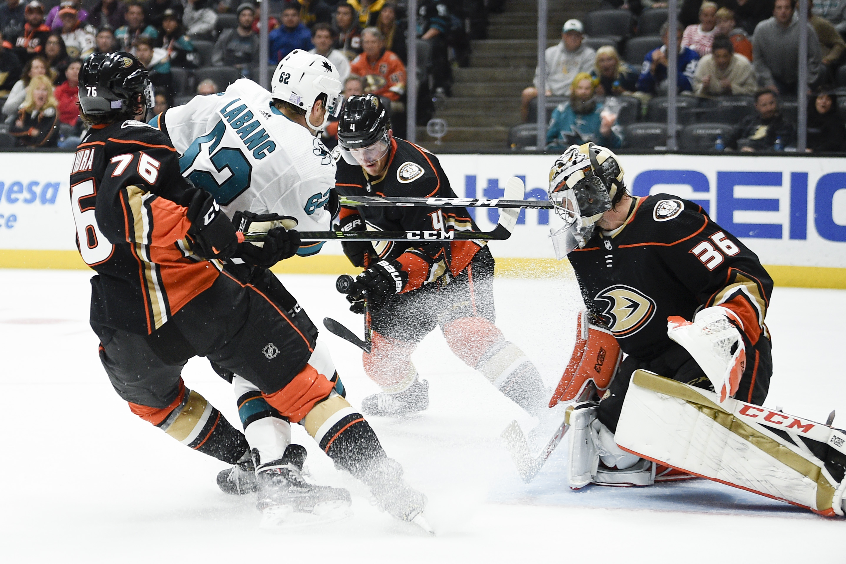 Nov 14, 2019; Anaheim, CA, USA; Anaheim Ducks defenseman Cam Fowler (4) and San Jose Sharks right wing Kevin Labanc (62) battle for the puck in front of goalie John Gibson (36) during the third period at Honda Center.