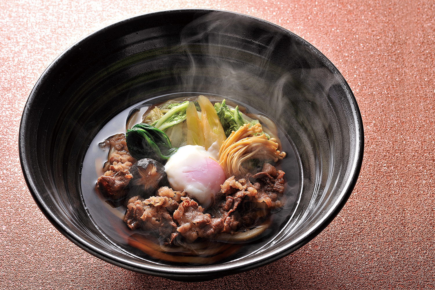Bowl of a Japanese soup, featuring a transparent brown broth, thinly sliced beef, thick udon noodles, a soft-boiled egg, and vegetables
