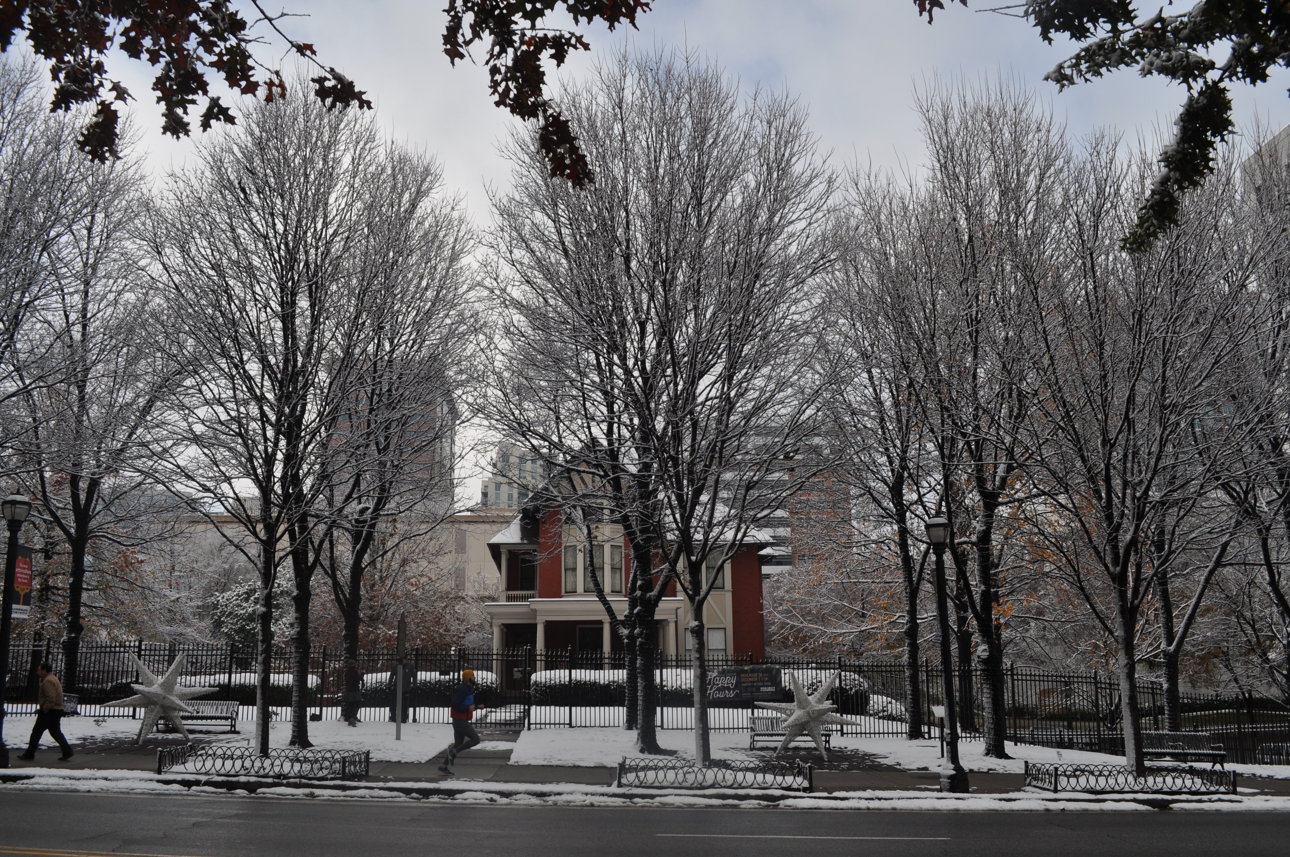 The old Colonial-style home and its lawn are coated in snow.