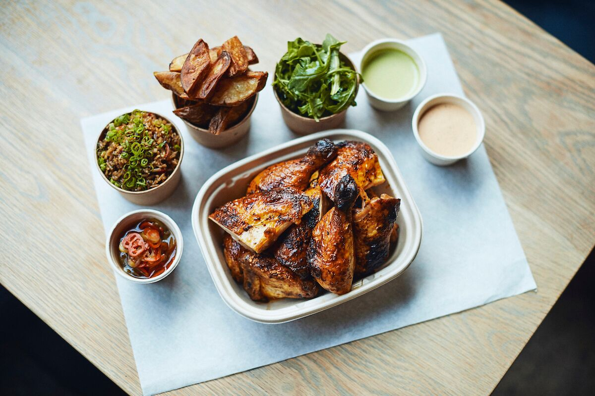 A table full of different dishes with a plate of rotisserie chicken in the center