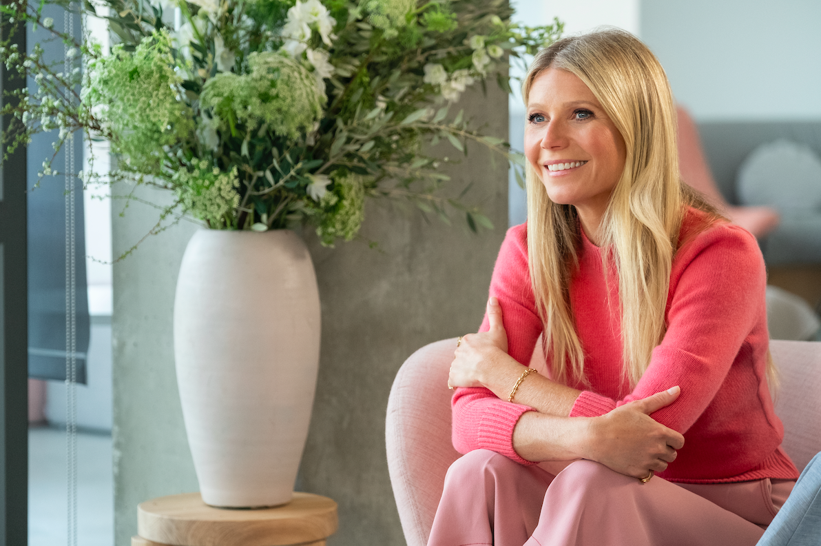 Gwyneth Paltrow sits on a couch.