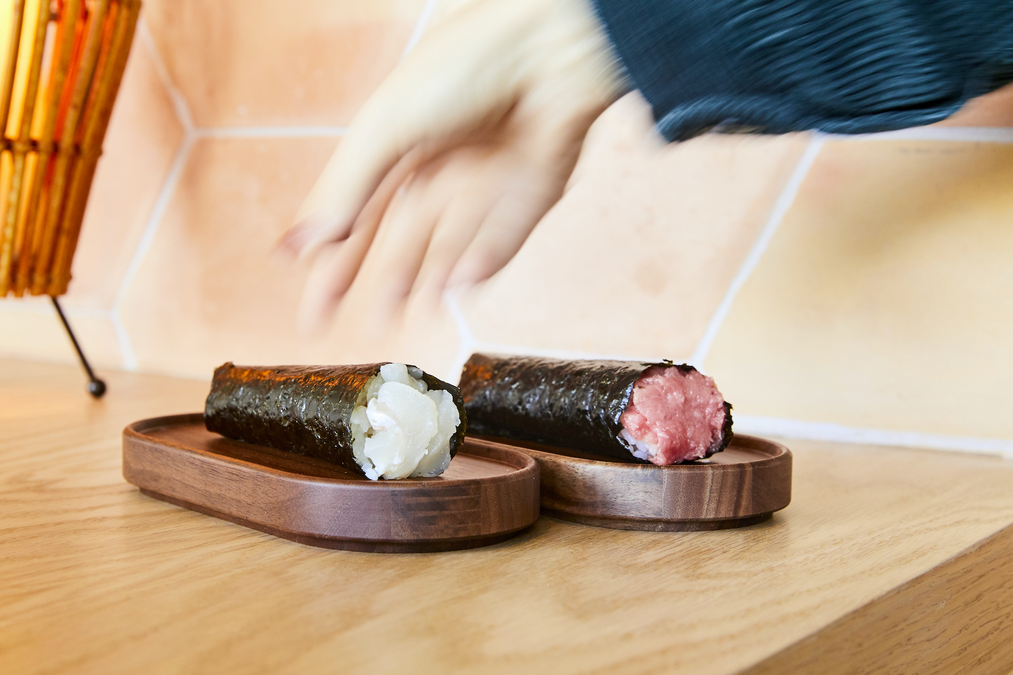 A hand blurs in to grab one of two sushi hand rolls on a wooden plate.