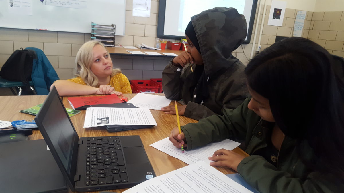 A teacher works with ninth grade students in an English Language Arts class at Aurora Central High School.