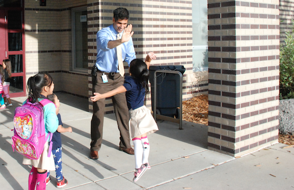 Maxwell Elementary principal Nivan Khosravi greets students as they arrive. Several weeks into the semester, he still had new students arriving.