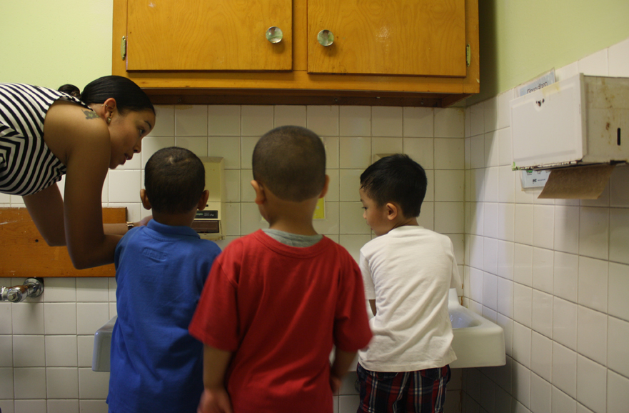 Pre-K teacher Khadija Prowell shows students how to wash their hands on the first day of school at Grand Street Settlement.