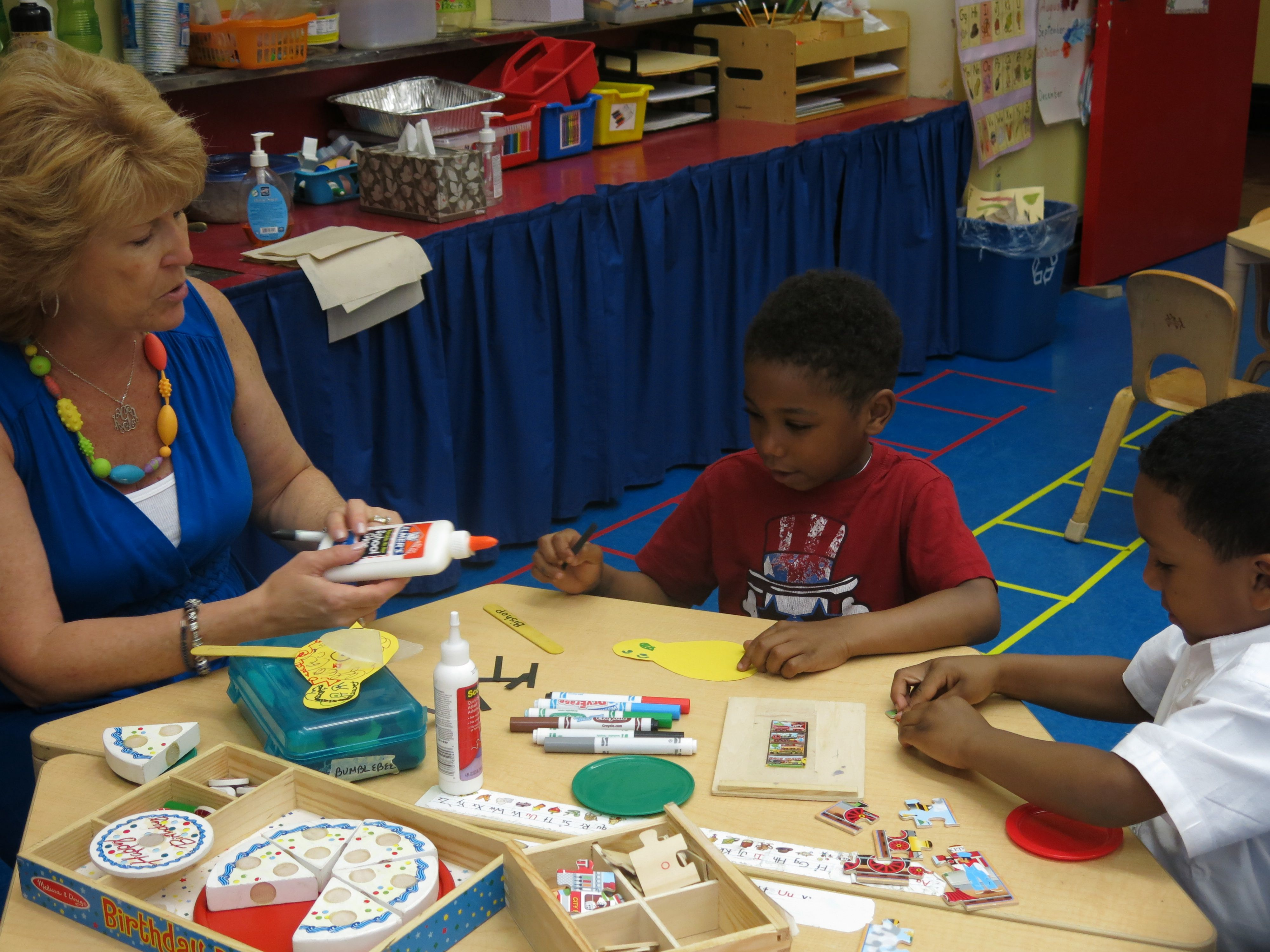 """A pre-K teacher at New Bridges Elementary works with two students in their classroom's """"math center."""""""