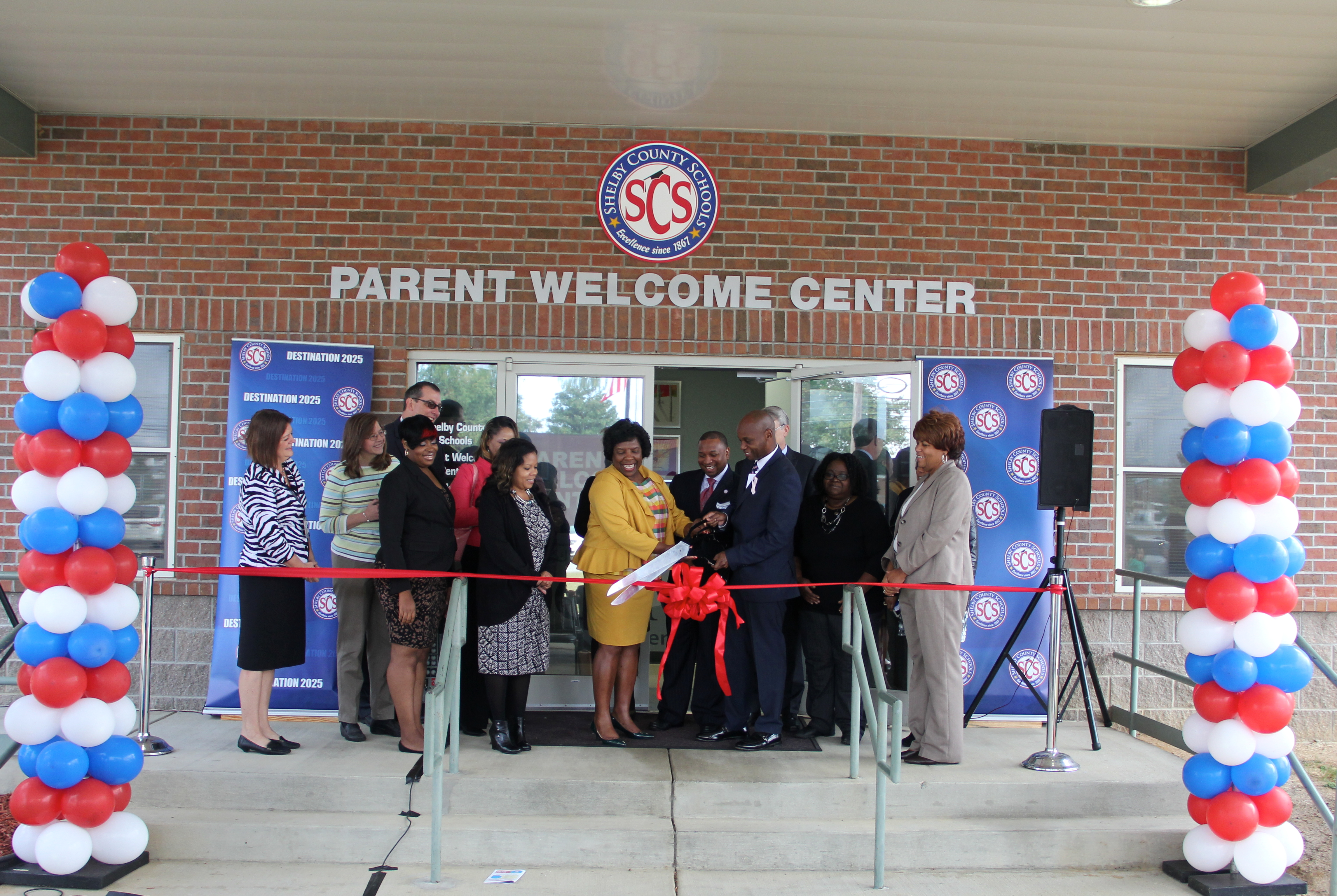 Surrounding by supporters, Superintendent Dorsey Hopson cuts the ribbon officially opening Shelby County Schools' new parent welcome center in Memphis.