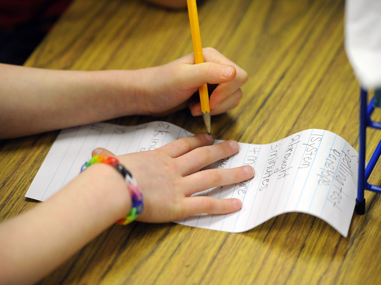 A close-up of a young student's hands as they work on a spelling test.