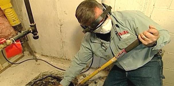 Person install a basement sump pump.