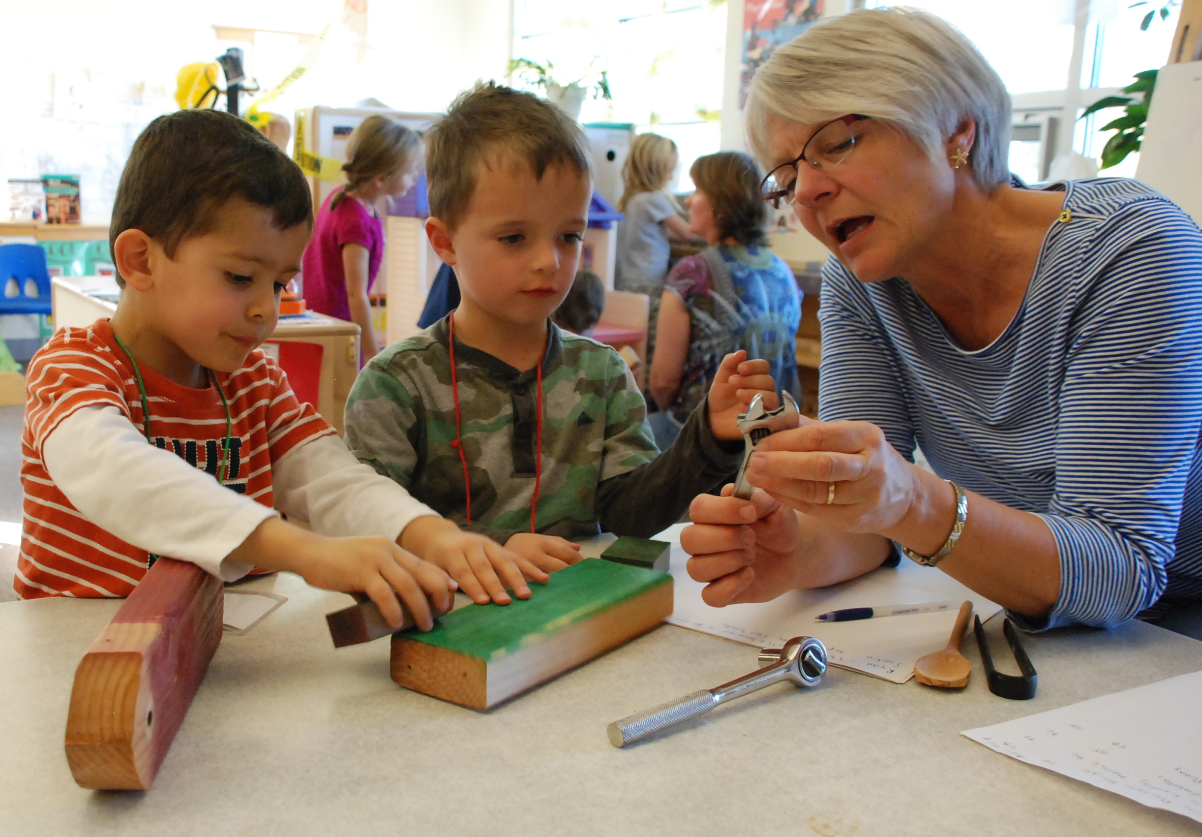 Teacher Dee Gilmore talks with two preschoolers at the Bal Swan Children's Center about tools.