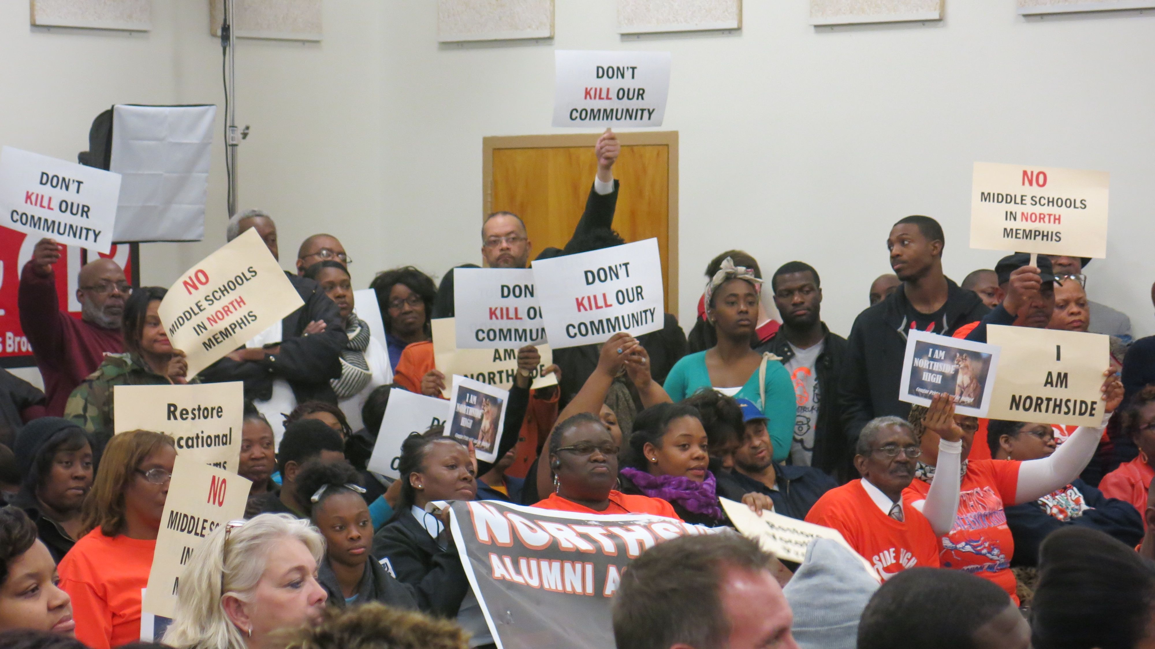 People hold aloft signs at school closings meeting.