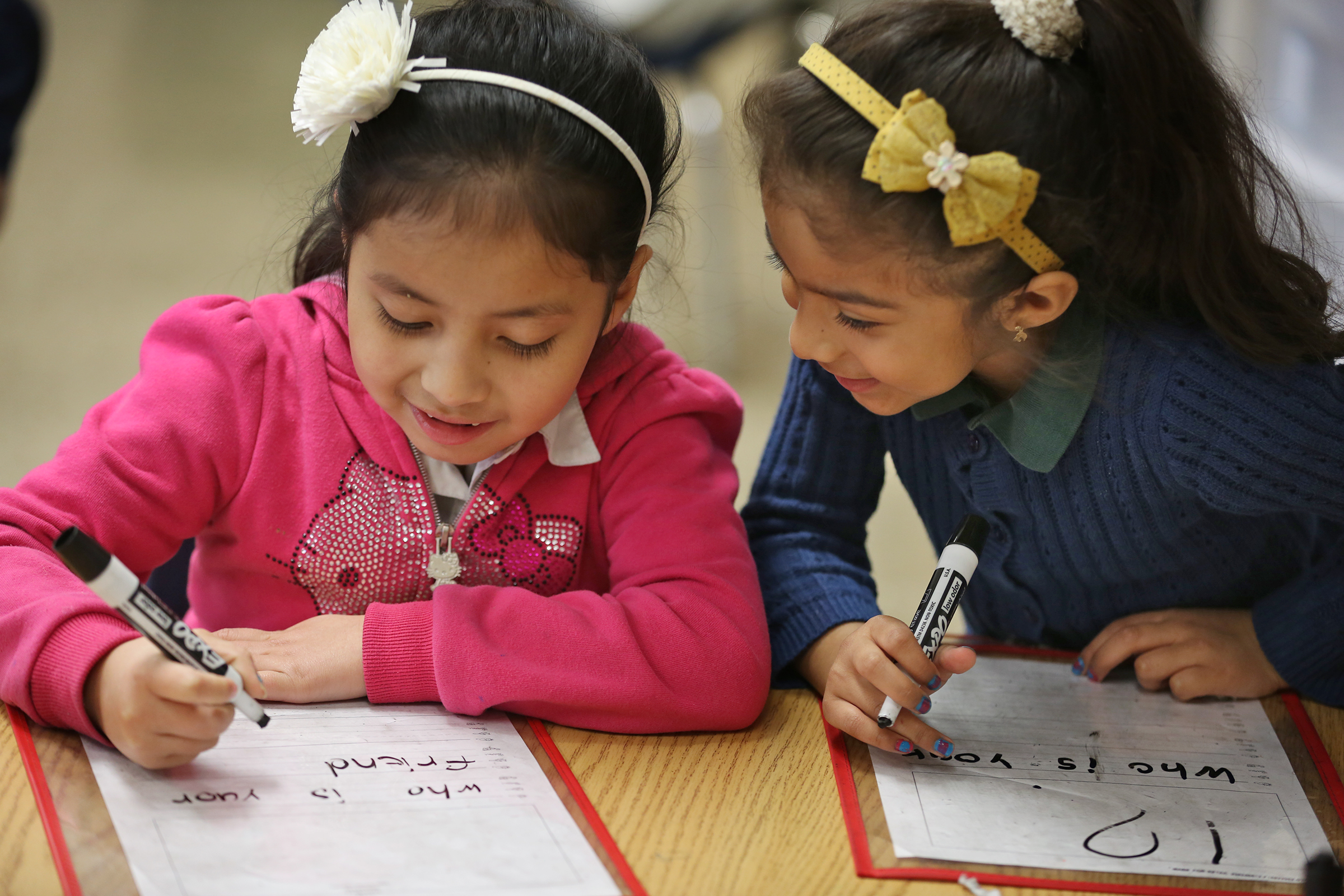 Kindergartners Ivania, left, and Jackie work on reading and writing at Enlace Academy.